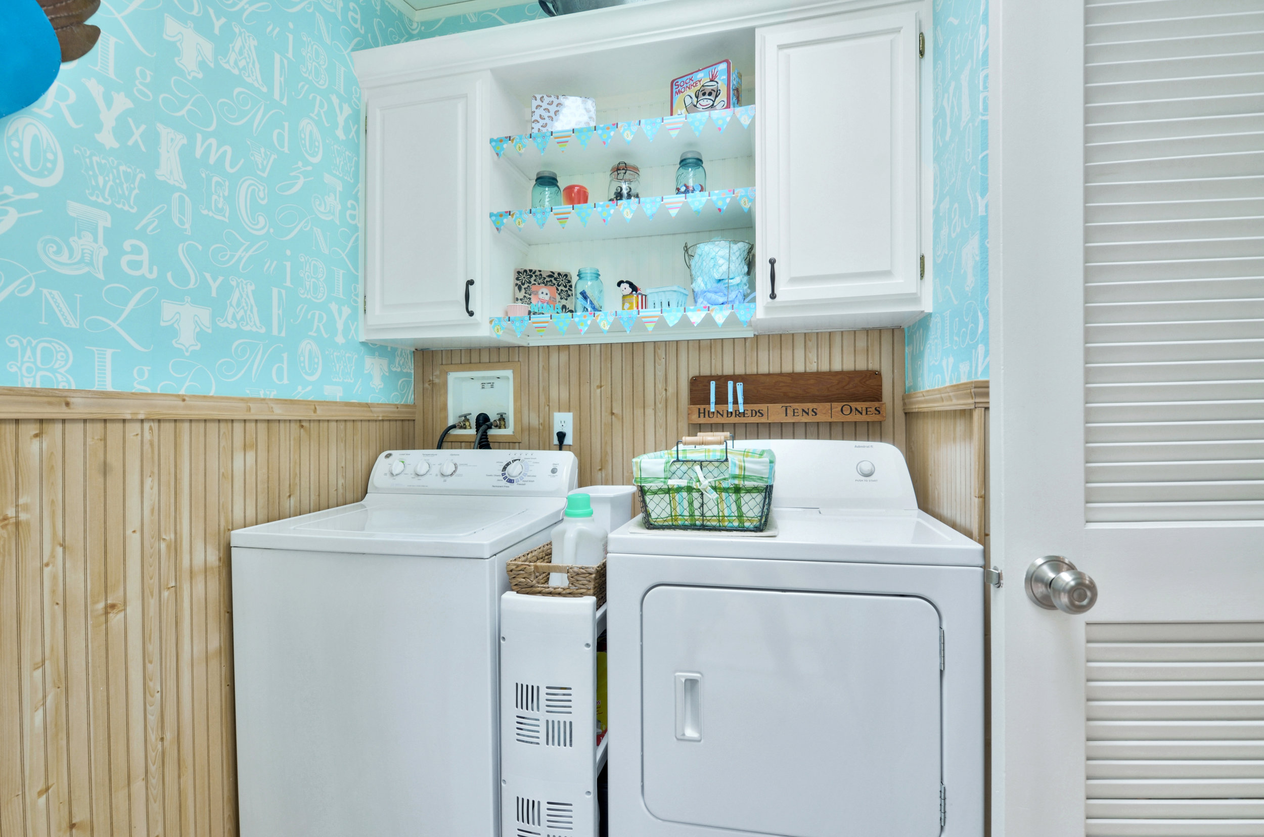 The laundry room isn't only functional and conveniently located off the kitchen, it's also super cute! There's a water hook-up in here if you'd like to install a utility sink. Shelves and cupboards above the washer and dryer give you a good spot for all your detergents, and a back door (with doggie door) leads out to the deck.