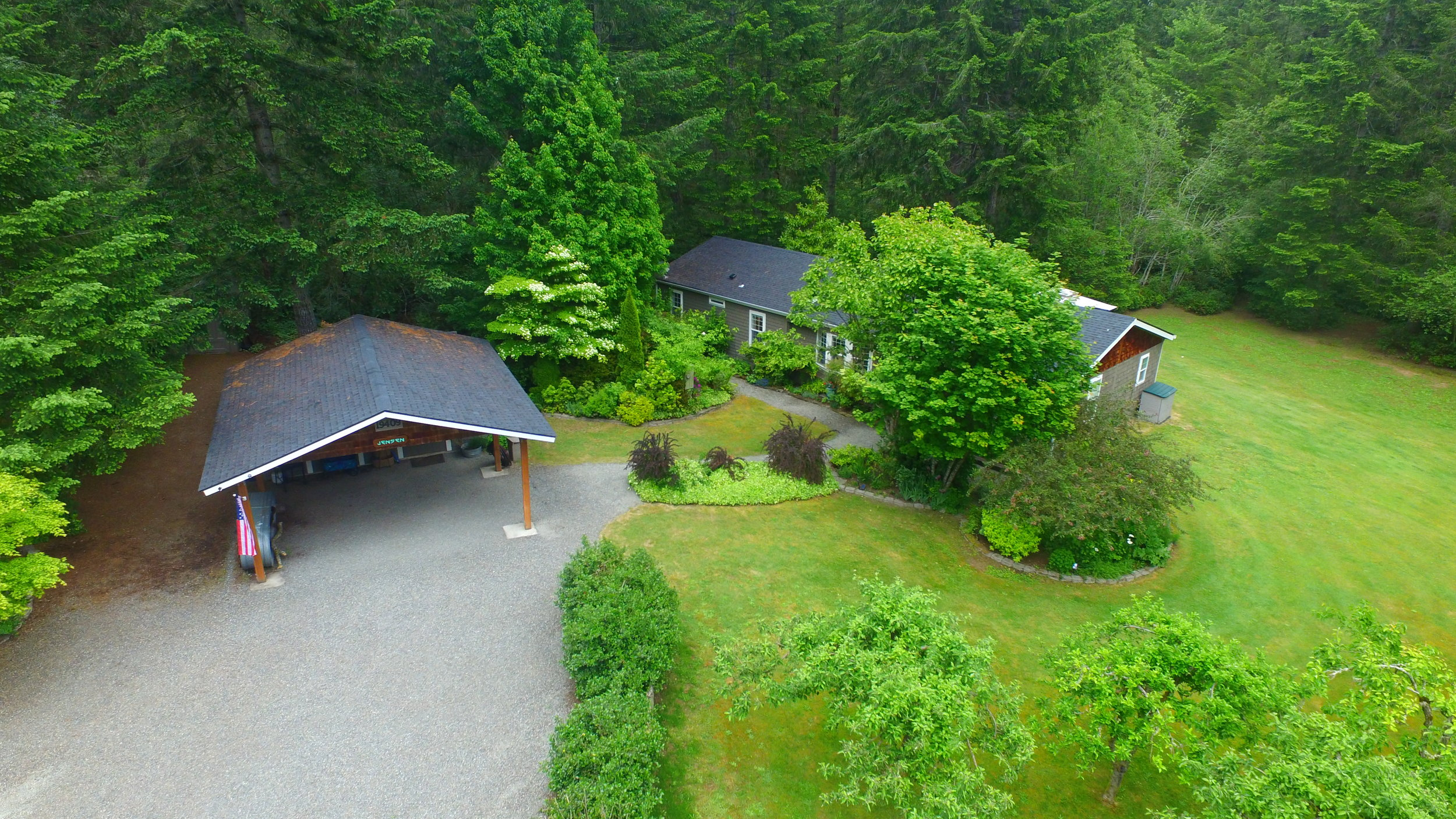 An overhead view of part of the gravel drive as well as the garden beds leading to the house. The lawn curves around the side, and extends all the way around the back of the home to the edge of the trees.