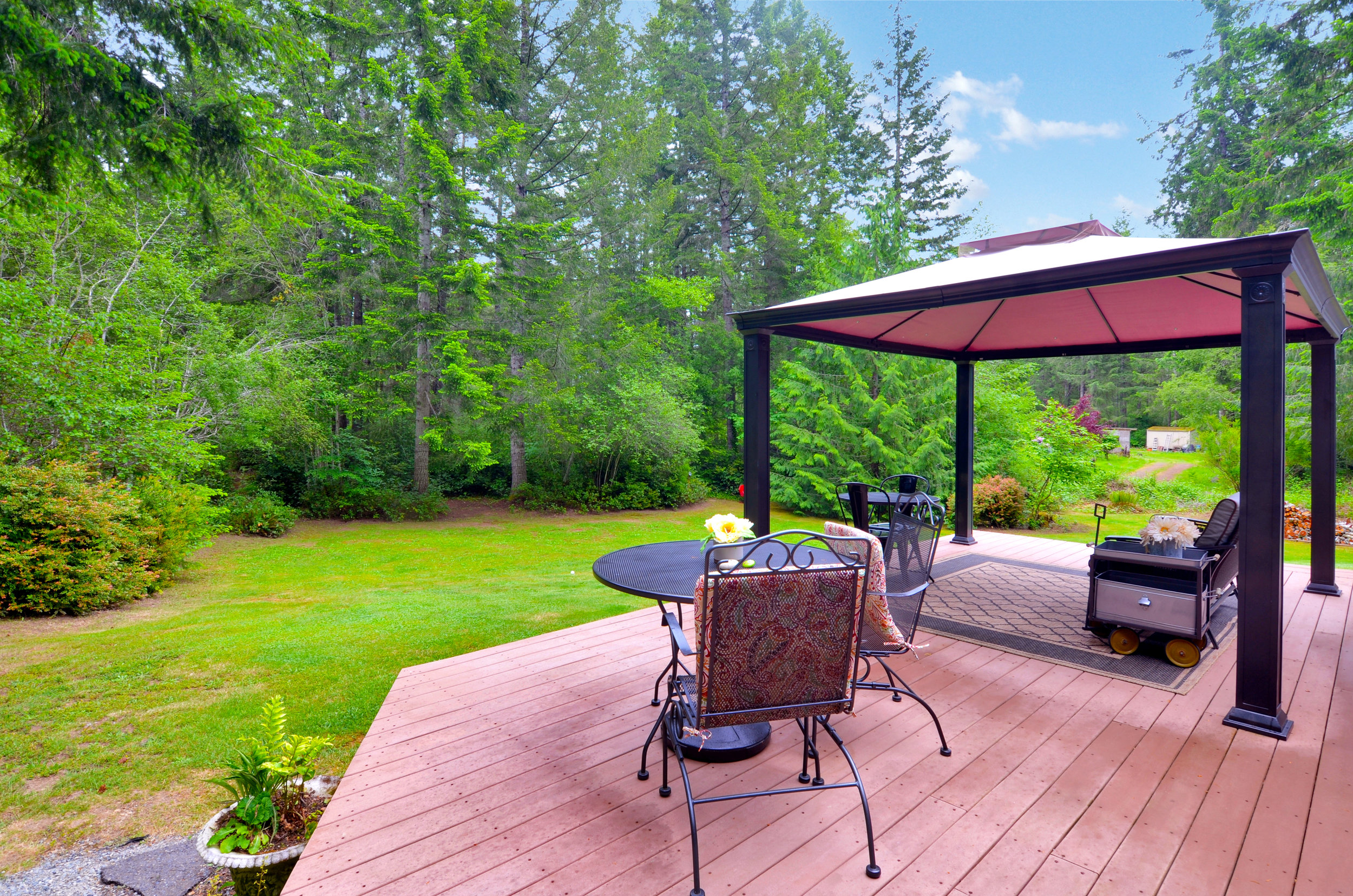 The spacious back deck overlooks the back yard and woods where Douglas fir, cedar, alder, and huckleberry thrive. The screen house stays, so you'll be all set to enjoy its shade this summer!