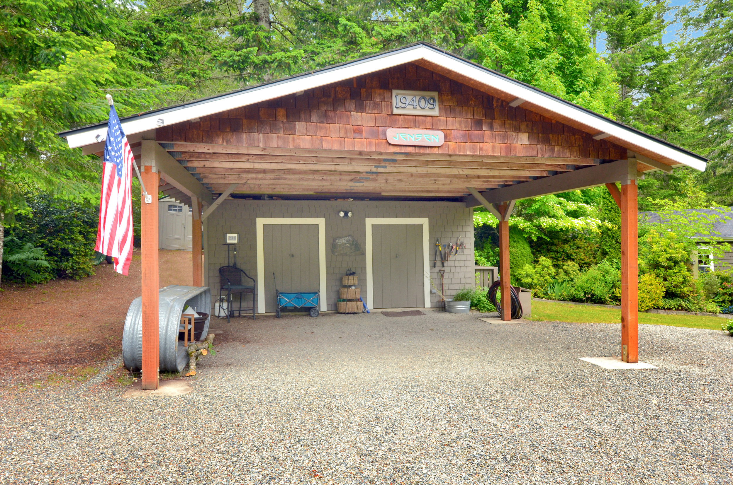 This 2 car 480 sq ft car port has a workshop and lean-to attached. It's a great spot for covered parking and there's plenty of additional parking in the gravel drive, including a spot for an RV.