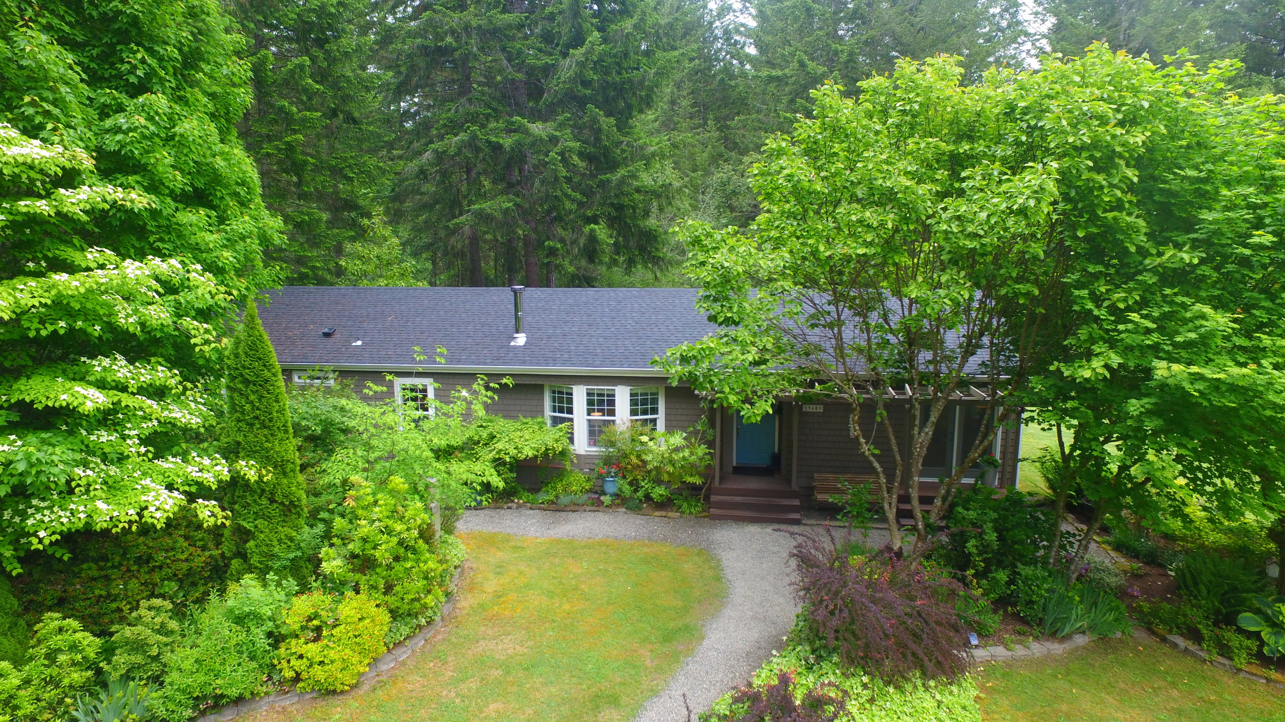 Meticulously maintained by the original homeowners, this cedar-shingled single-story manufactured home is surrounded by gravel paths and landscaped beds with acres of woods just beyond. Notice the beautiful landscaping trees such as dogwood and Japanese maple planted to compliment the native woodland. You'll find hostas, hydrangeas, lilac, and so many more shrubs and flowers in this carefully tended garden.