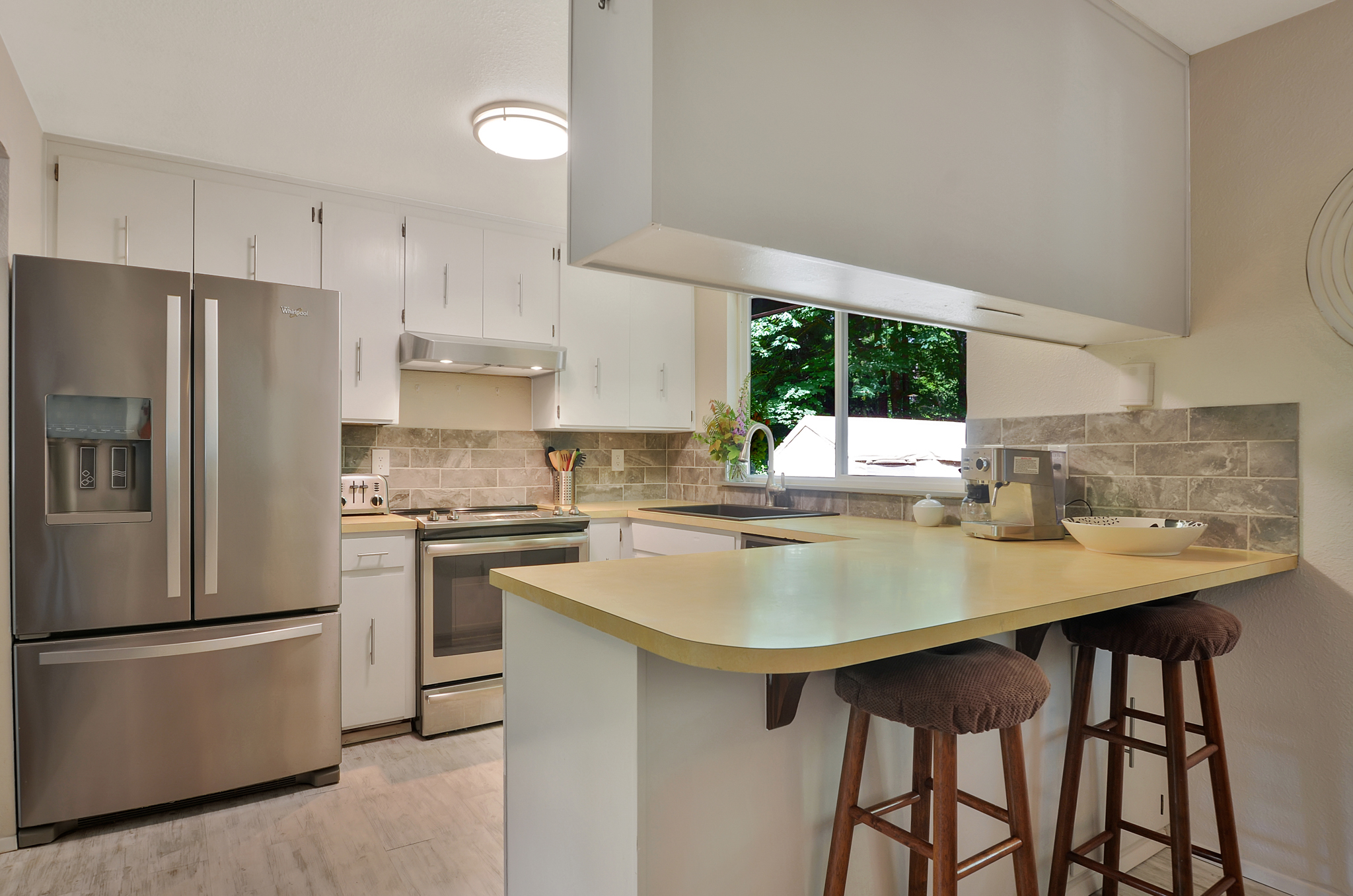 Bar stools are a great spot to stick your friends or kids while getting meals or a snack ready. This design also ensures a good amount of counter space for chopping, stirring, and baking. The new refrigerator has a water filter, ice maker, and freezer drawer.