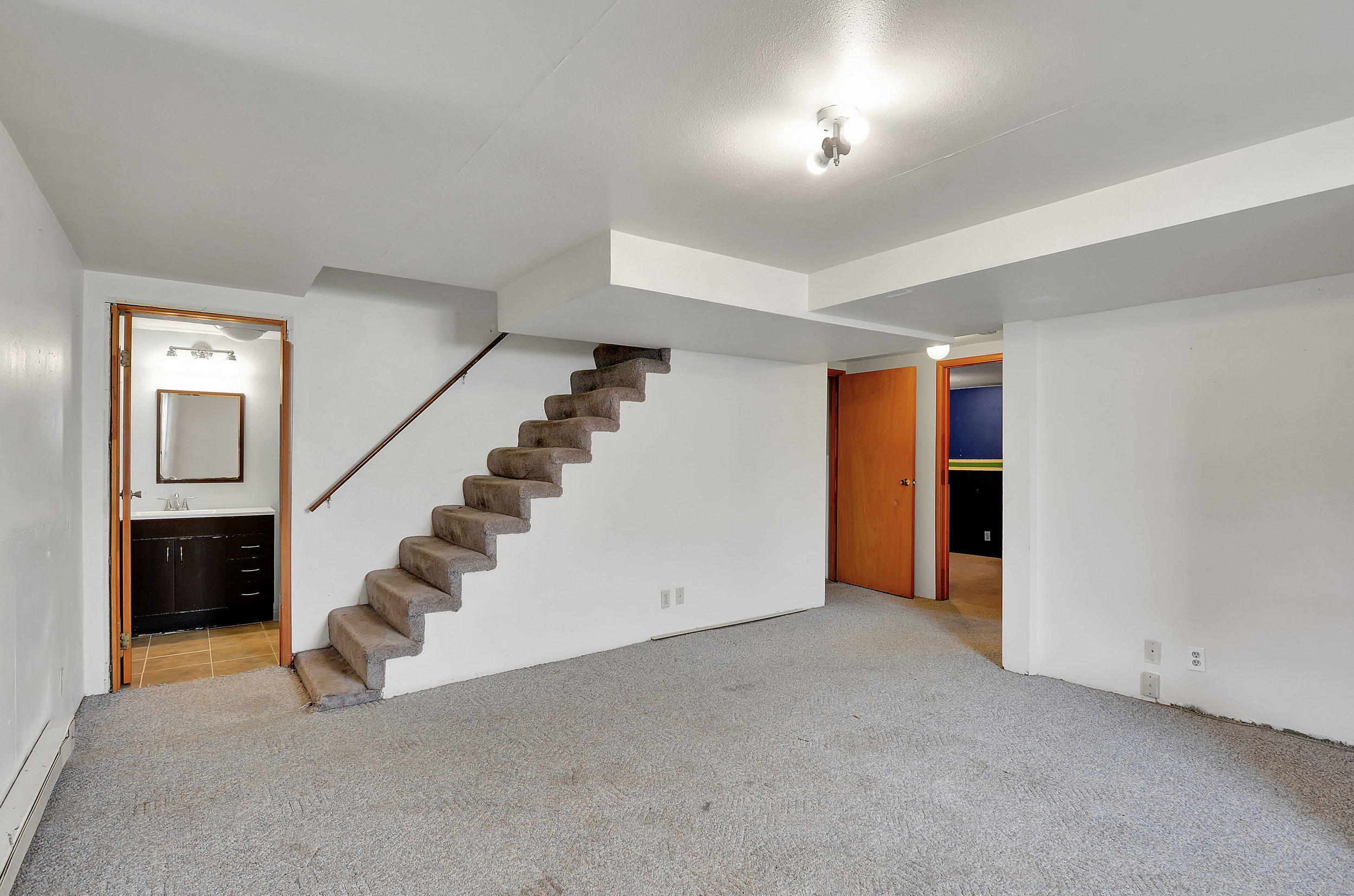 The finished basement with a 3/4 bath at the bottom of the stairs.