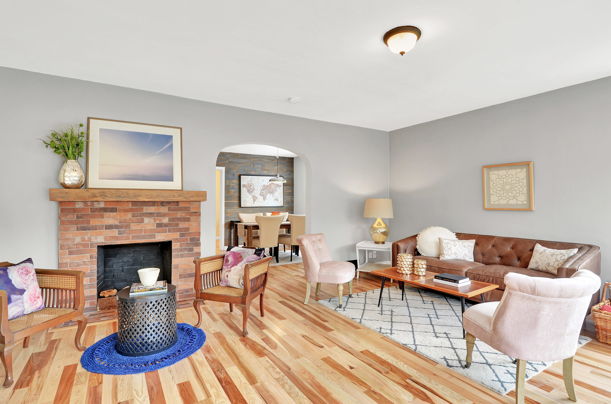 The living room features a fireplace with a brick hearth and solid mantle, and an attractive archway into the dining room.