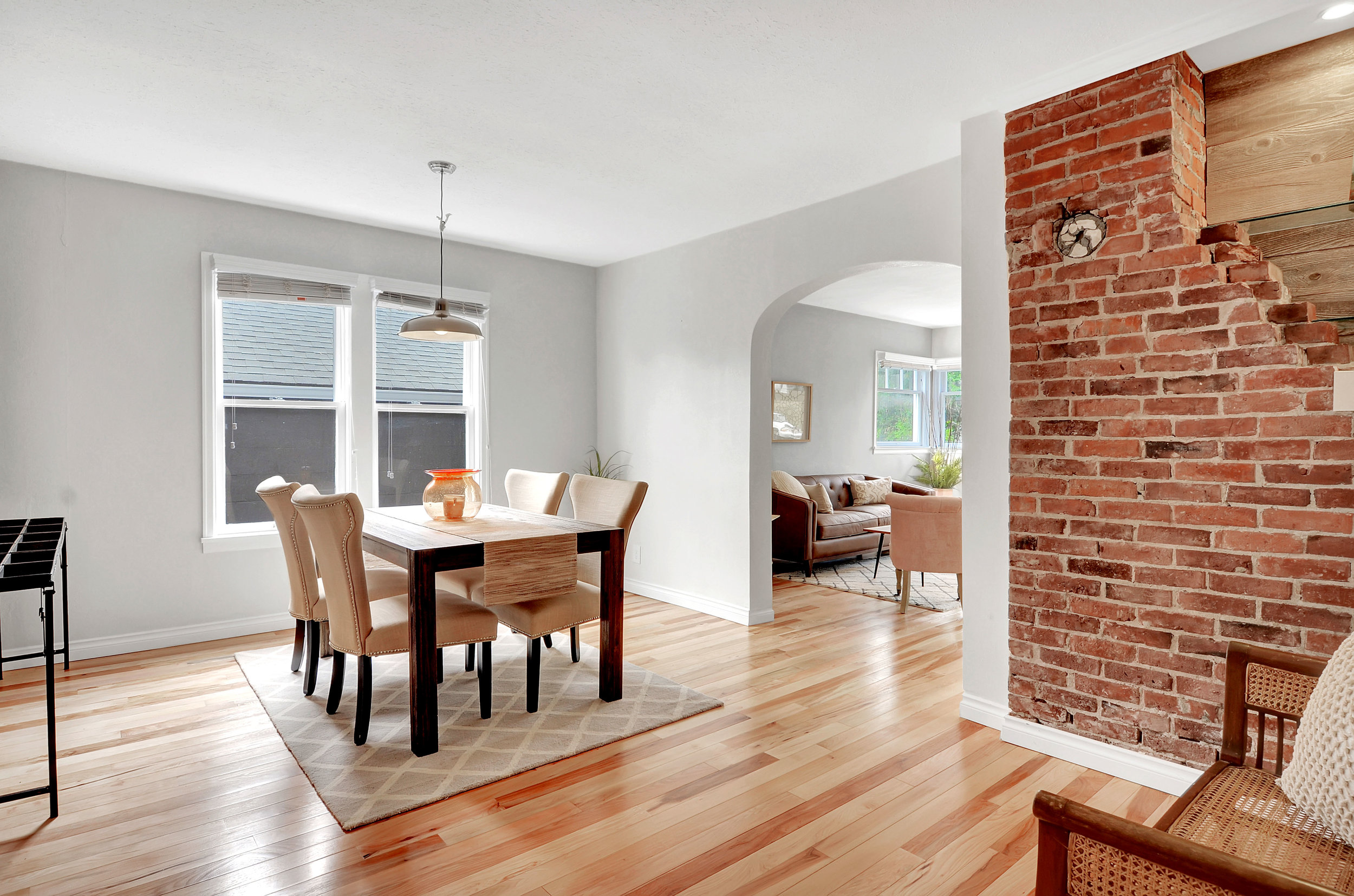 There's plenty of texture and interest in this dining room with the exposed brick, graceful archway, and rustic planking on the wall. Set up candles and a mini bar display on the the chimney back.