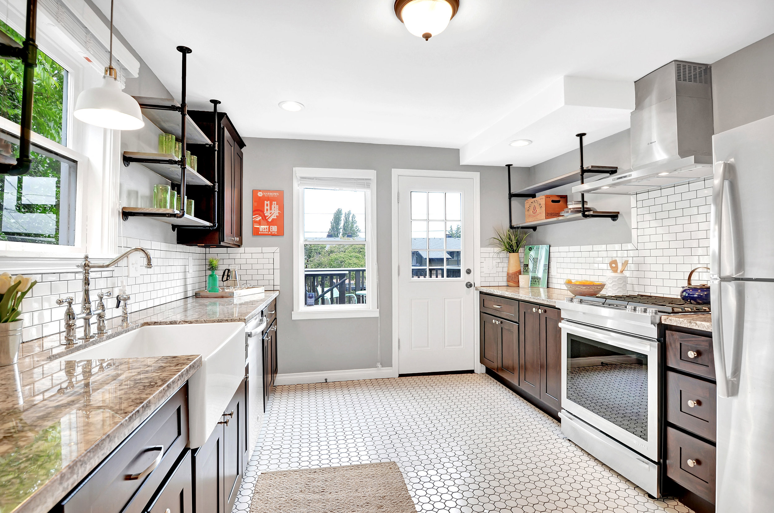 We love this kitchen: octagonal tile flooring, subway tile backsplash, stone counters, gas range, farmhouse sink, and industrial pipe shelving.