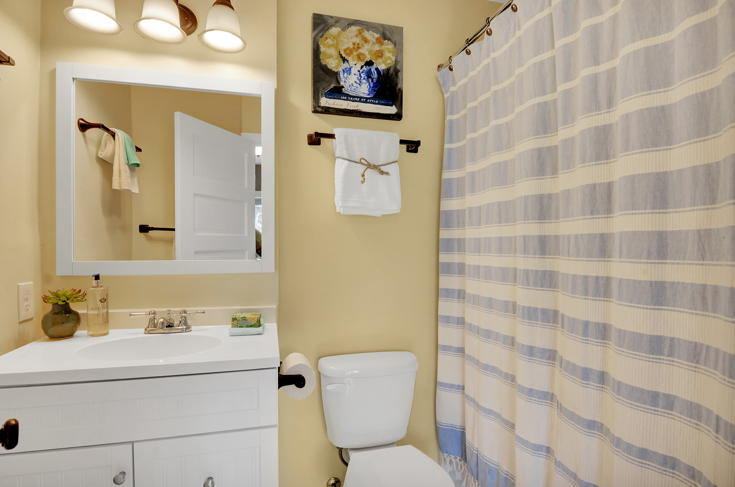 The private full bath has a tile floor, and tile in the shower/tub combo with a classic white vanity and mirror.