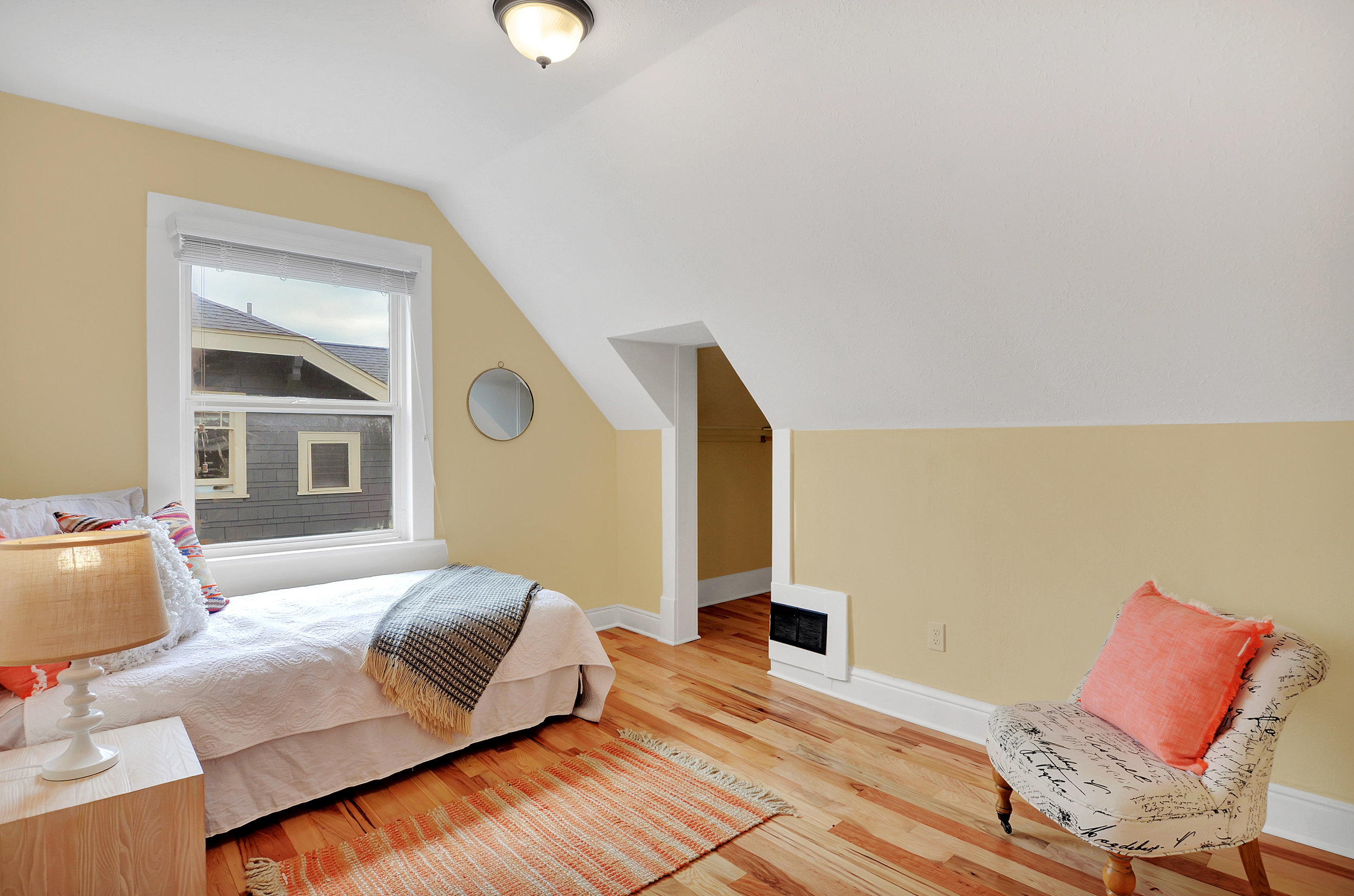 The 2nd of 3 bedrooms, perfect for kids, teens, or guests with a cozy curved ceiling and hardwood floors.