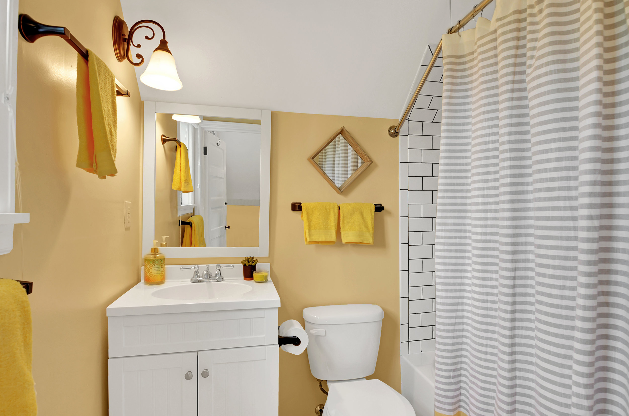 The 3rd full bath is located upstairs off the landing for easy access from the bedrooms. Find the same octagonal floor tile and white subway tile shower/tub area.