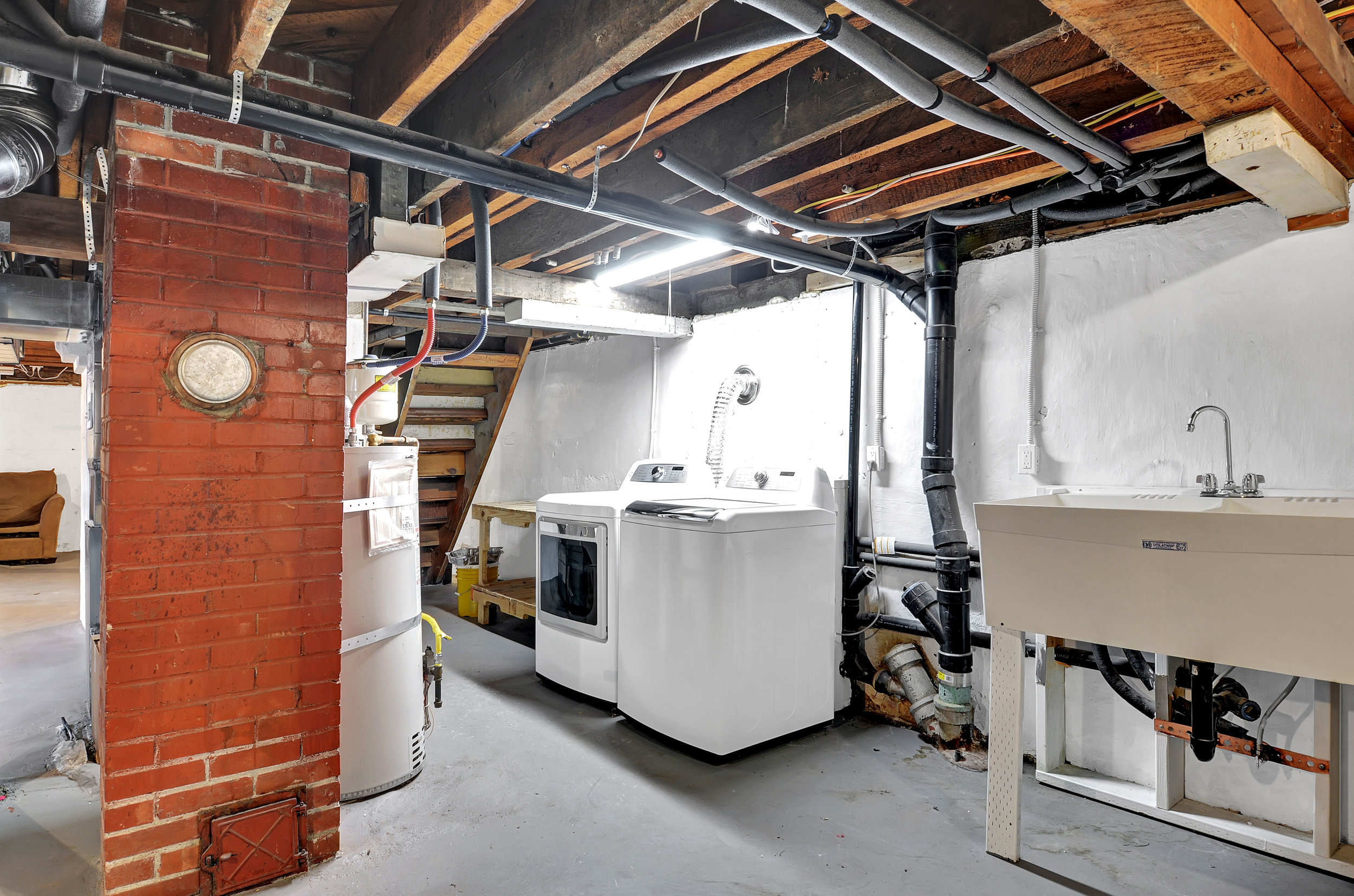 The laundry area is located in the basement with a large, practical utility sink beside.