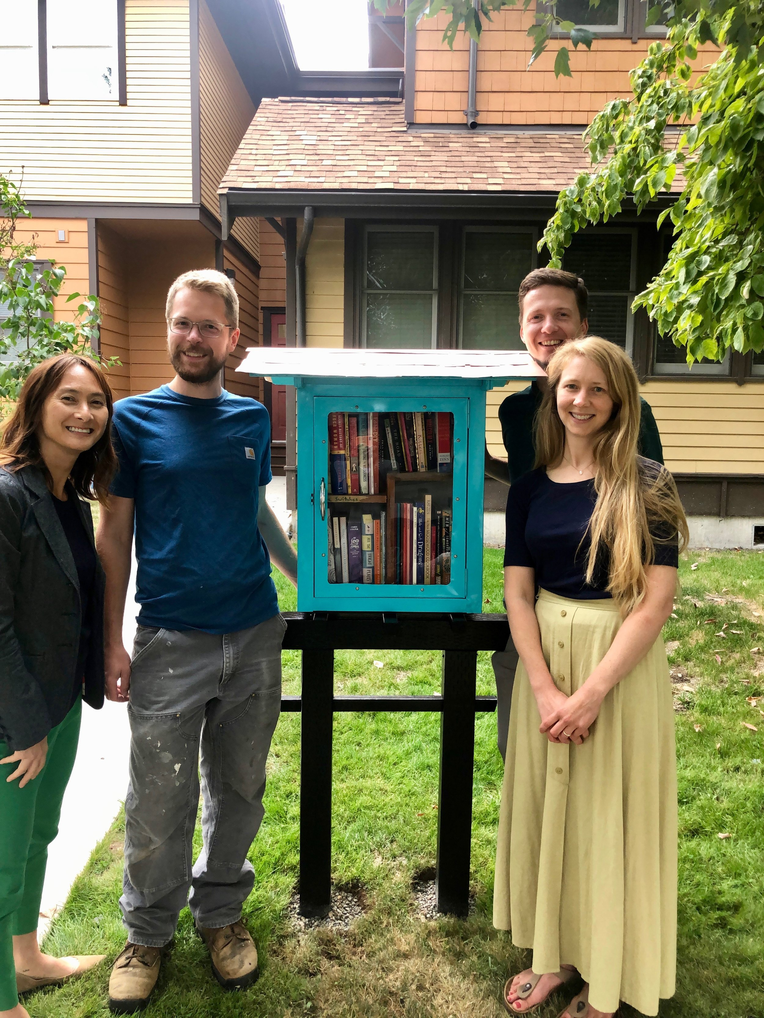 We love the new Peace Library! Jamie Brooks, Aaron Skwirut (designer & builder), Michael & Gretchen Duggan gathered around the library on installation day.