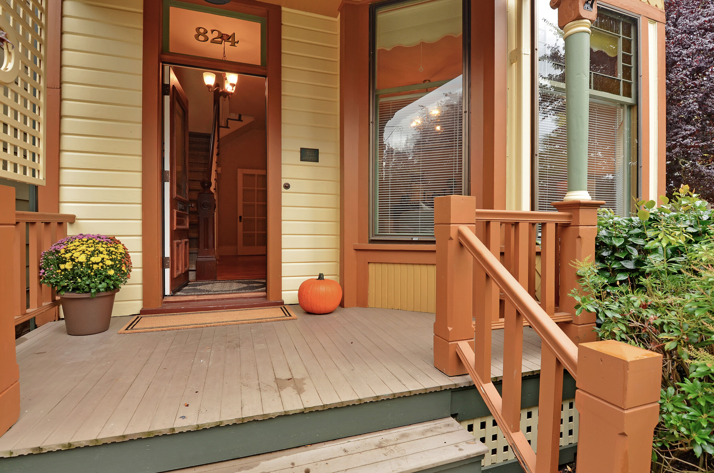 A covered front porch faces M St. and overlooks the carefully landscaped front yard with its masonry walls and paved paths.