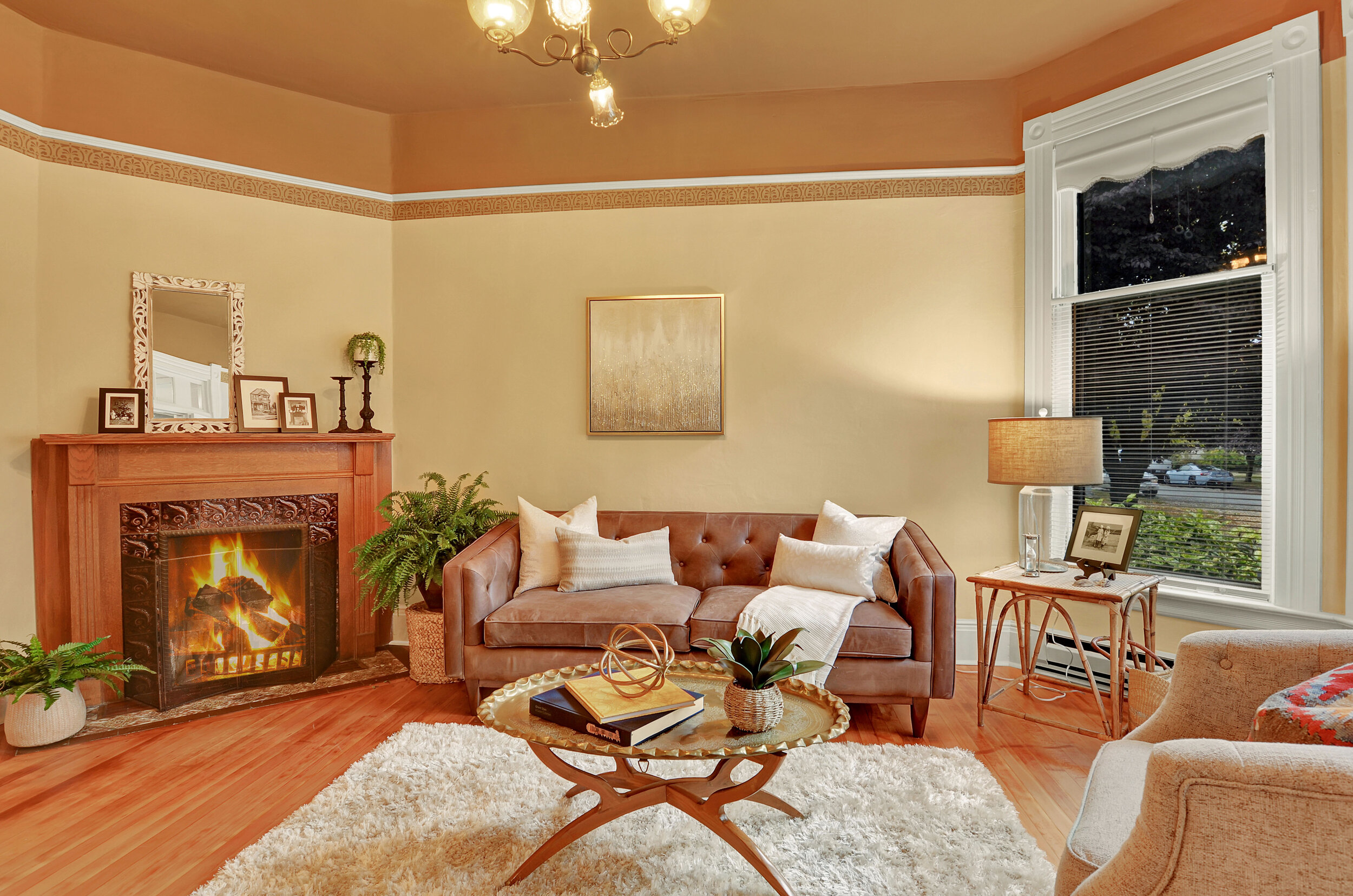 An oak fireplace built in the Rumford style with Victorian glaze tiles and stenciled scrollwork adorn the living room.