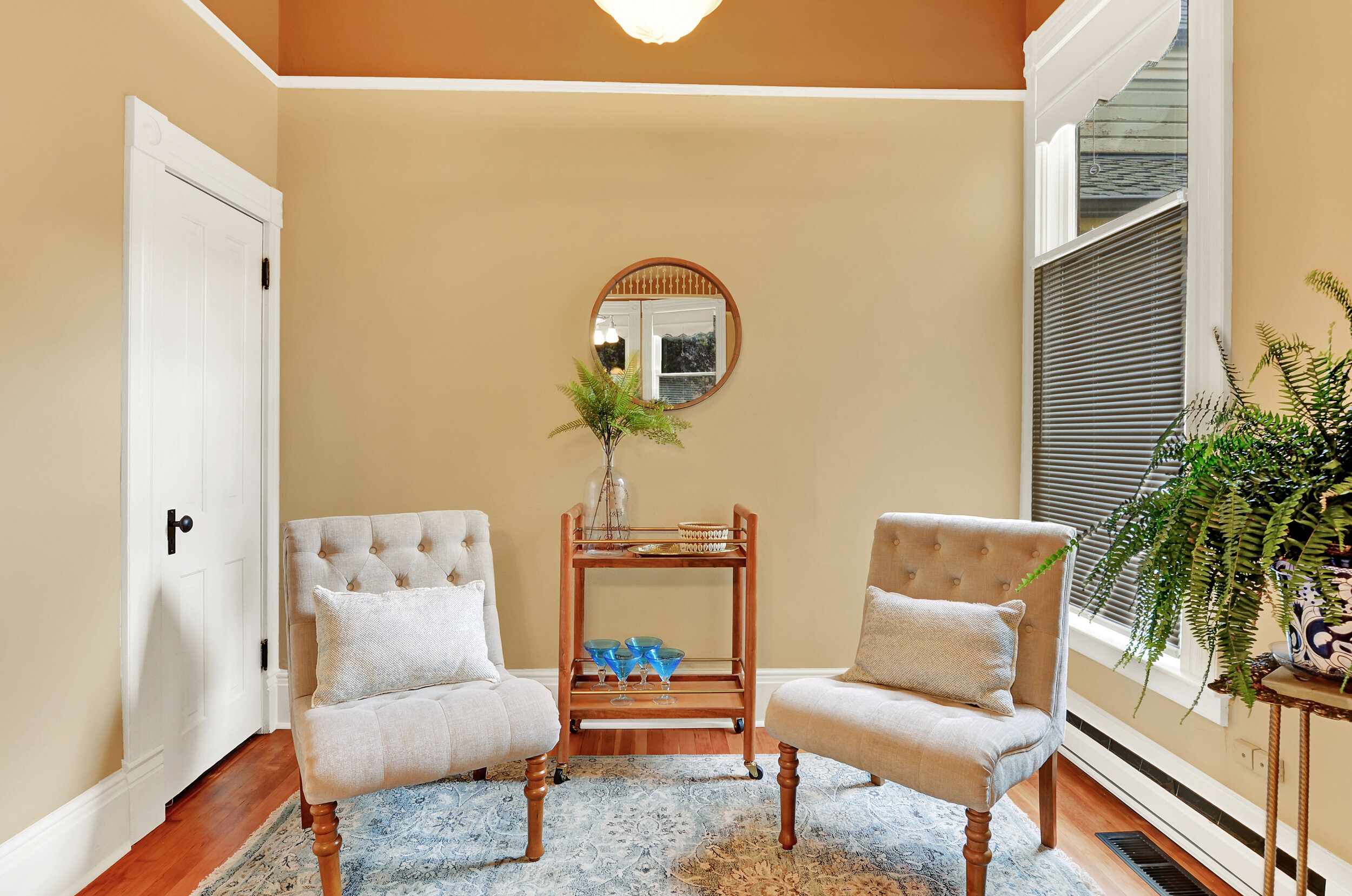A cased opening from the dining room invites you to this sitting room overlooking the back yard, a pleasant spot for a piano, additional seating, or a desk and bookshelf.