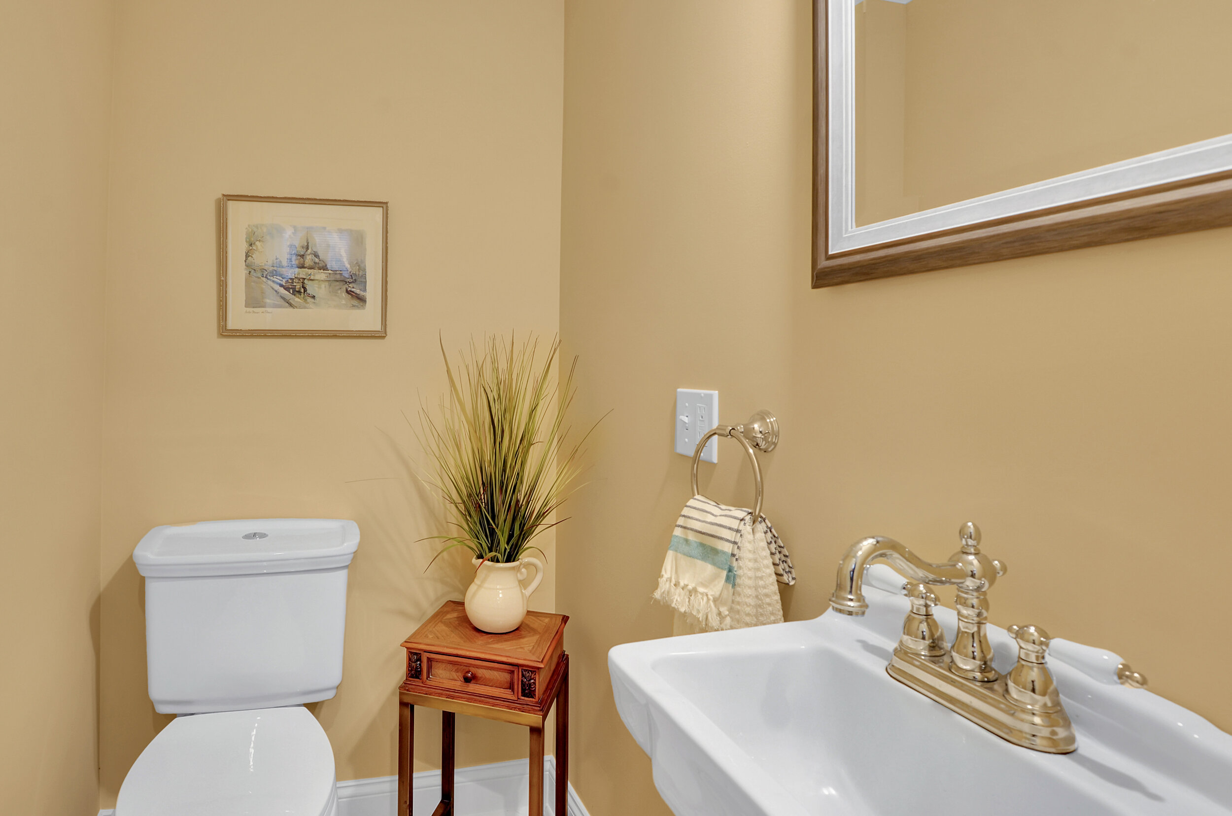 A crisp half bath is situated on the main level, in a private spot outside the kitchen.