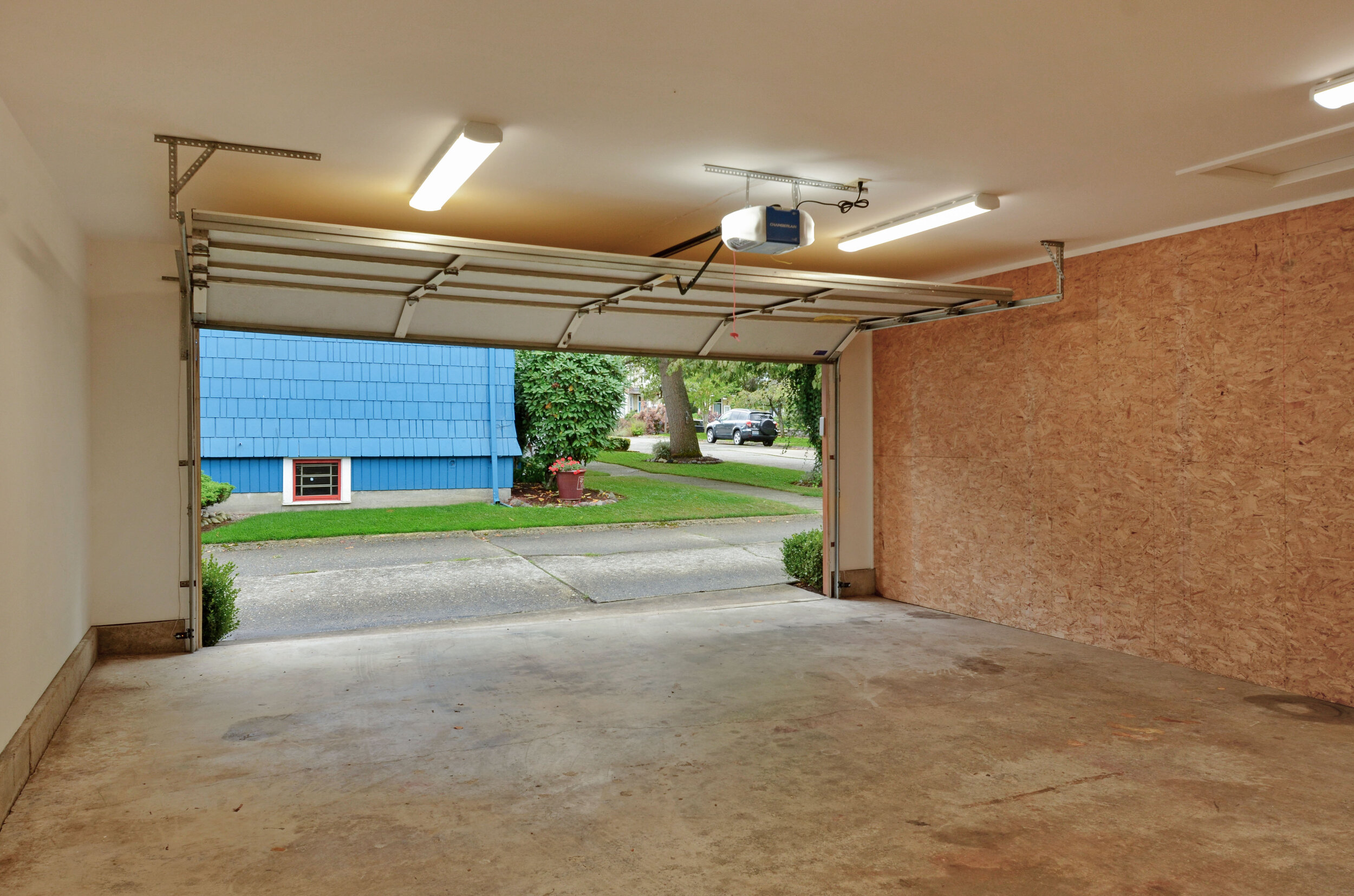 An automatic door opens from the paved alley into a clean bright space. A window on the east wall of the garage overlooks the back yard and garden.