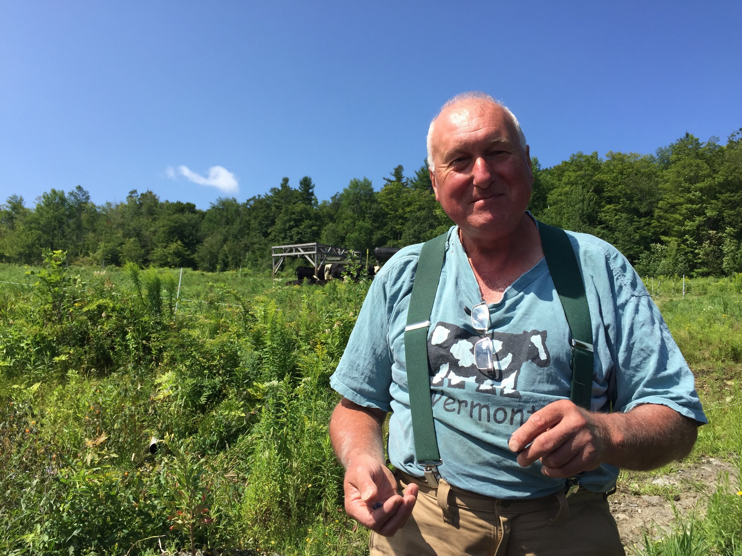 Geof dolman, the farmer, with cows in the background, and cows on his heart