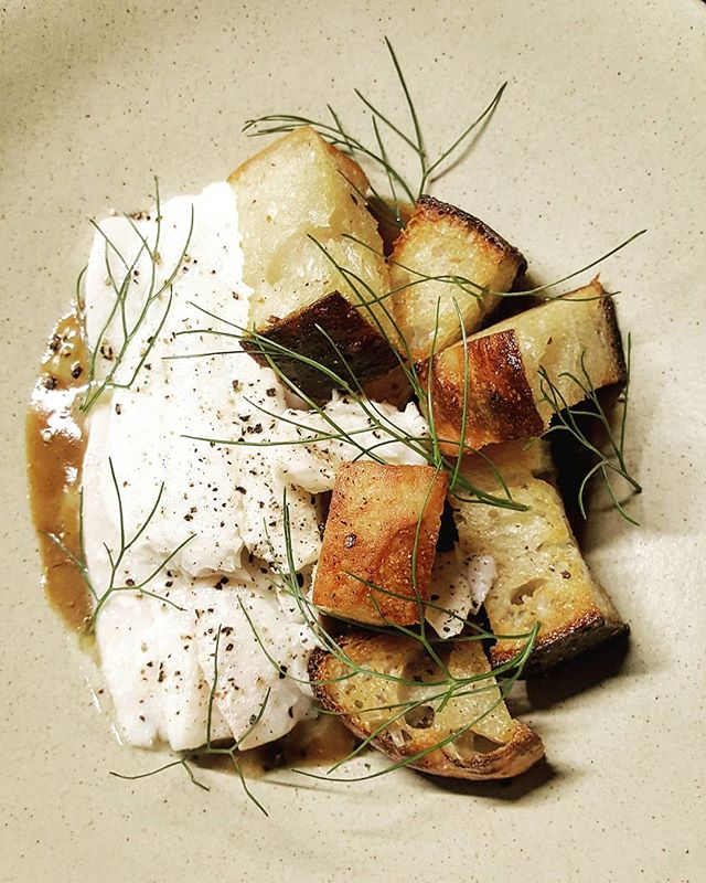 Butter poached flounder with focaccia croutons on a bed of jus gras topped with dill and cracked peppercorn