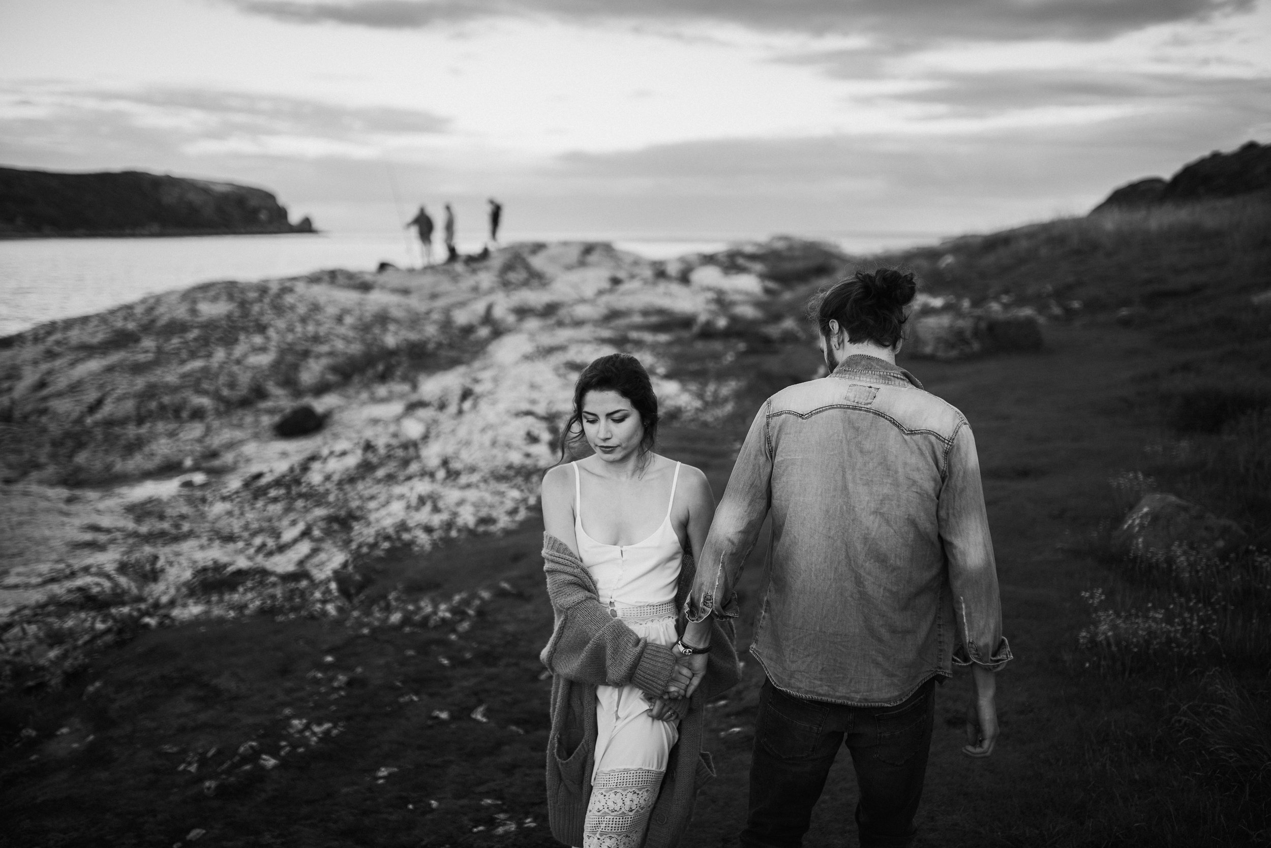 black and white photo of the couple walking on the northern Irish coast.jpg