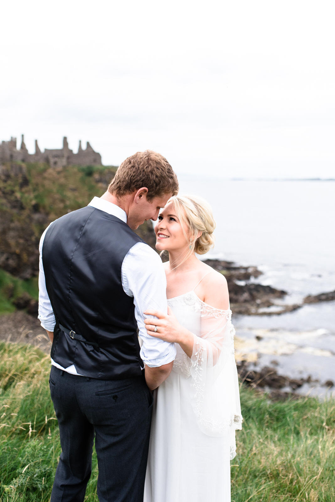 fine art dunluce castle elopement in ireland in sage and white, vows reading on the cliff of northern ireland, bo and luca wedding dress, couple hugging on the cliff-1.jpg