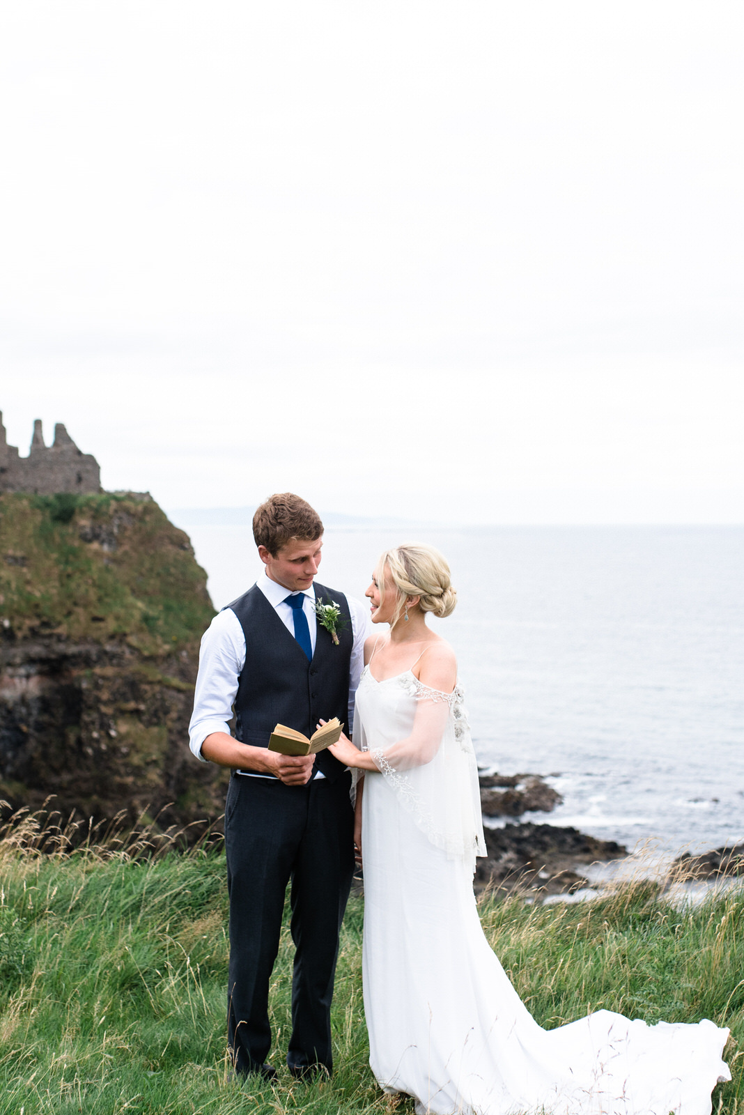 fine art dunluce castle elopement in ireland in sage and white, vows reading on the cliff of northern ireland-1.jpg