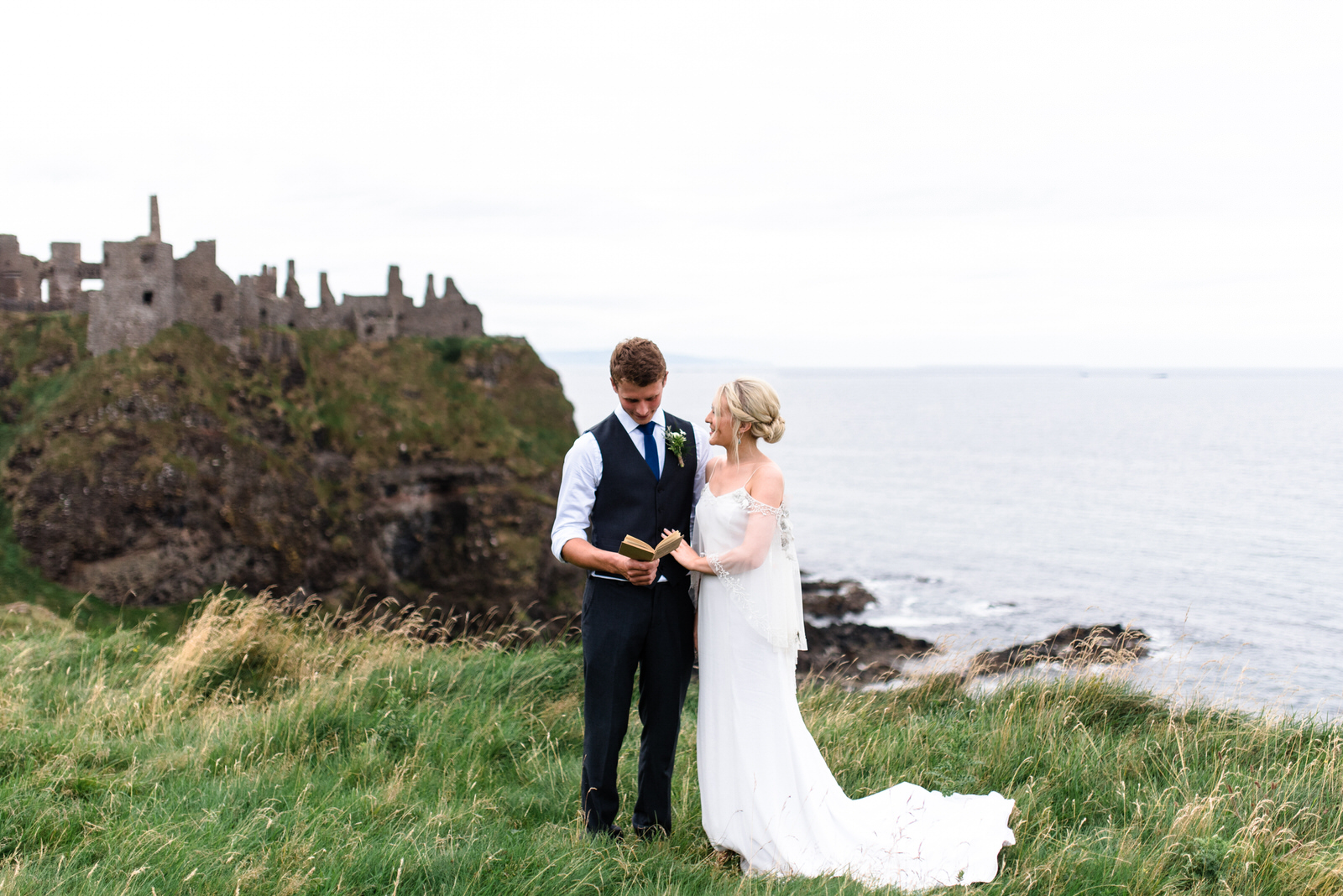 fine art dunluce castle elopement in ireland in sage and white, vows reading on the cliff of northern ireland, wedding day-1.jpg