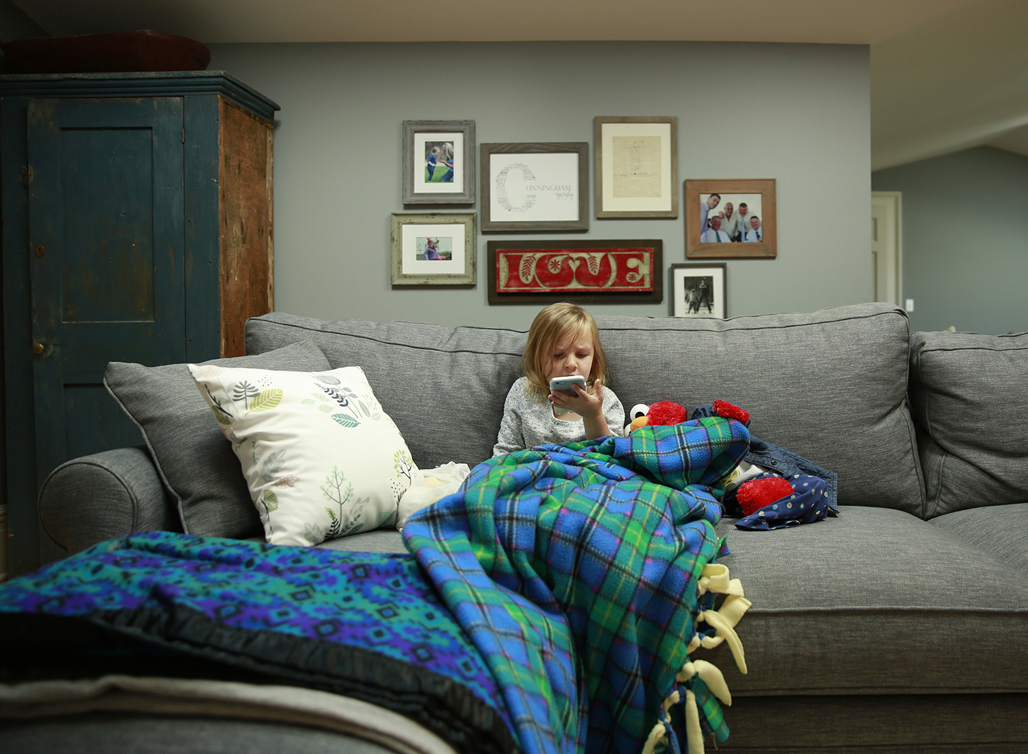 Copy of little girl playing with mom's cell phone during in-home photo session