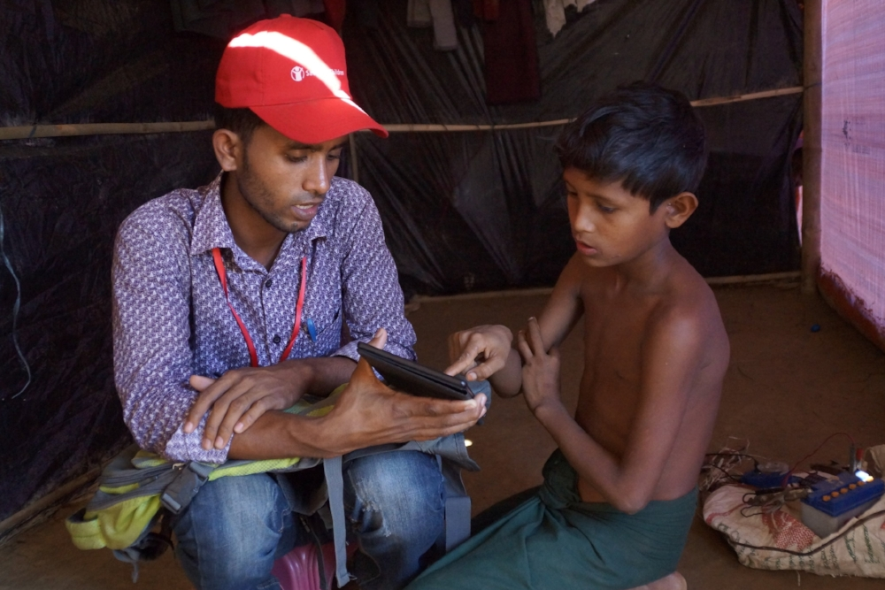 A Rohingya child using the digital tool with a trained individual.