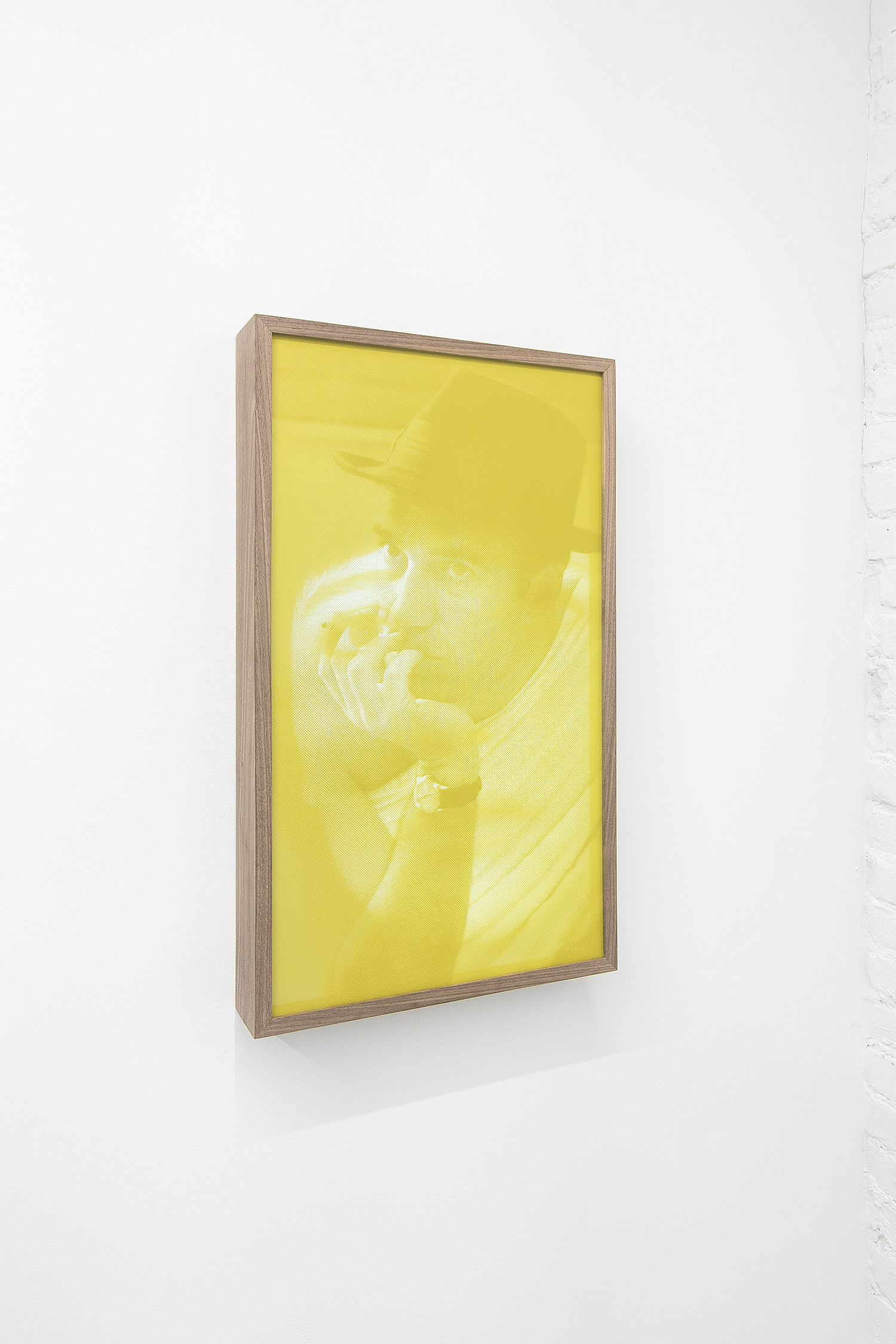 "I prefer you blonde. - I prefer you without a hat,  2019  Yellow silkscreen fabric, epoxic silkscreen on plexiglass, 32"" professional display and wood. Video: H264, 1920 x 1200px, 11:43 min. loop. 43.2 x 73.6 x 8.5 cm"