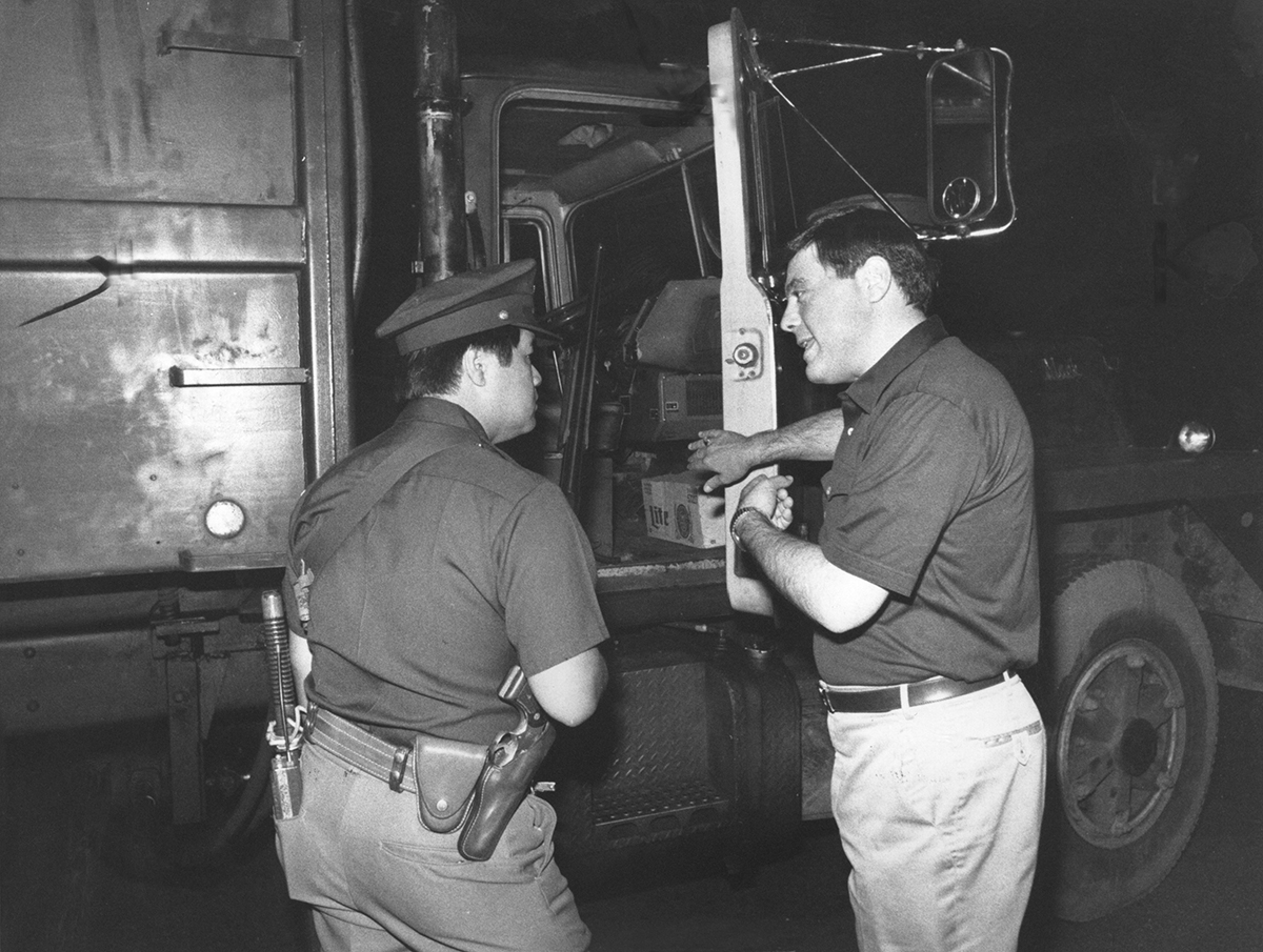 Buddy directs a Providence policeman into the cab of a garbage truck in July 1981.  Buddy fired striking garbagemen and hired a private company to drive the trucks, guarded by shotgun-toting police officers.   Courtesy of Providence Journal/John L. Hanlon.