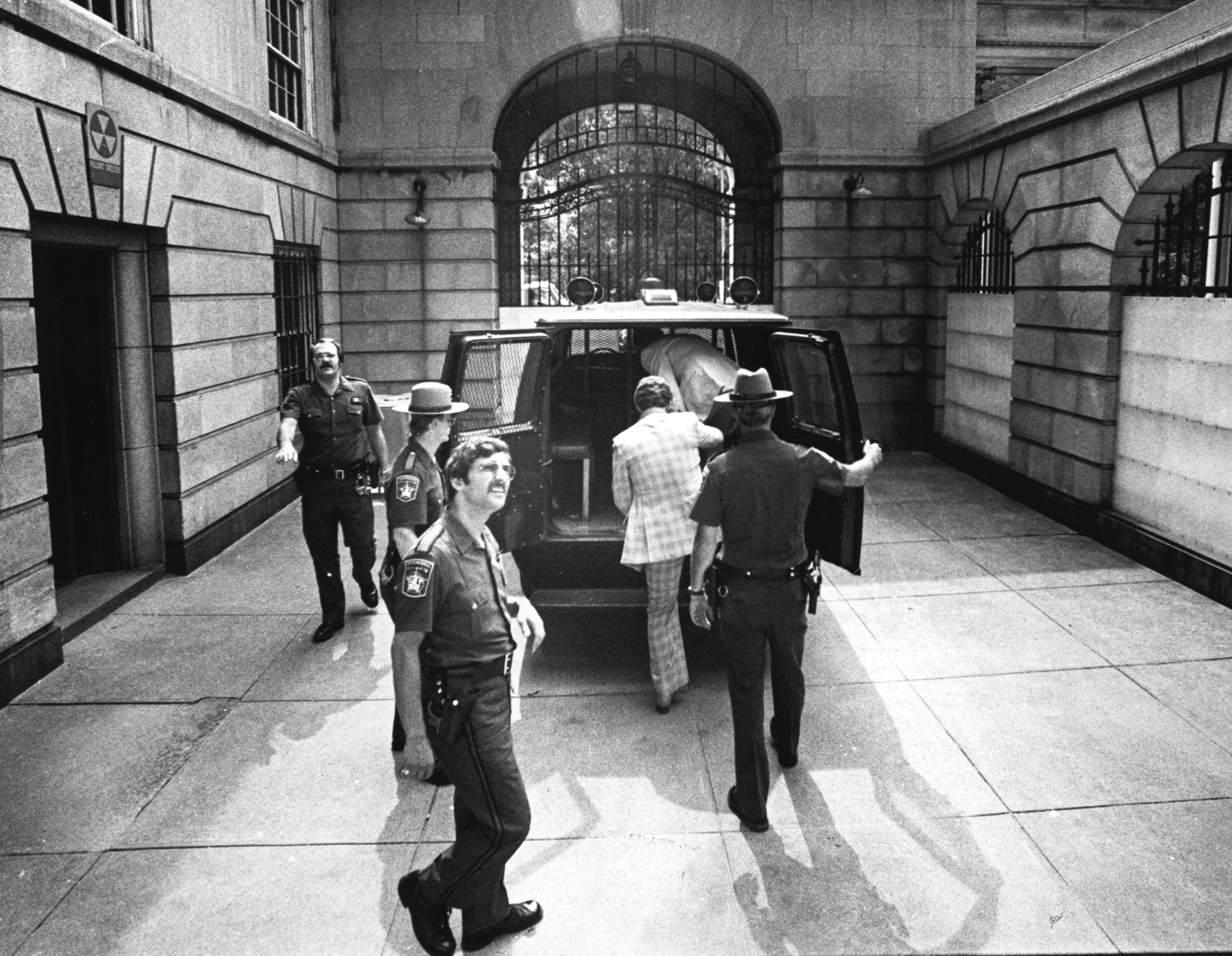 In August 1979, Jerry Tillinghast climbs into a van at Superior Court on his way to prison for the murder of George Basmajian.  Courtesy of the Providence Journal/Michael Delane y.