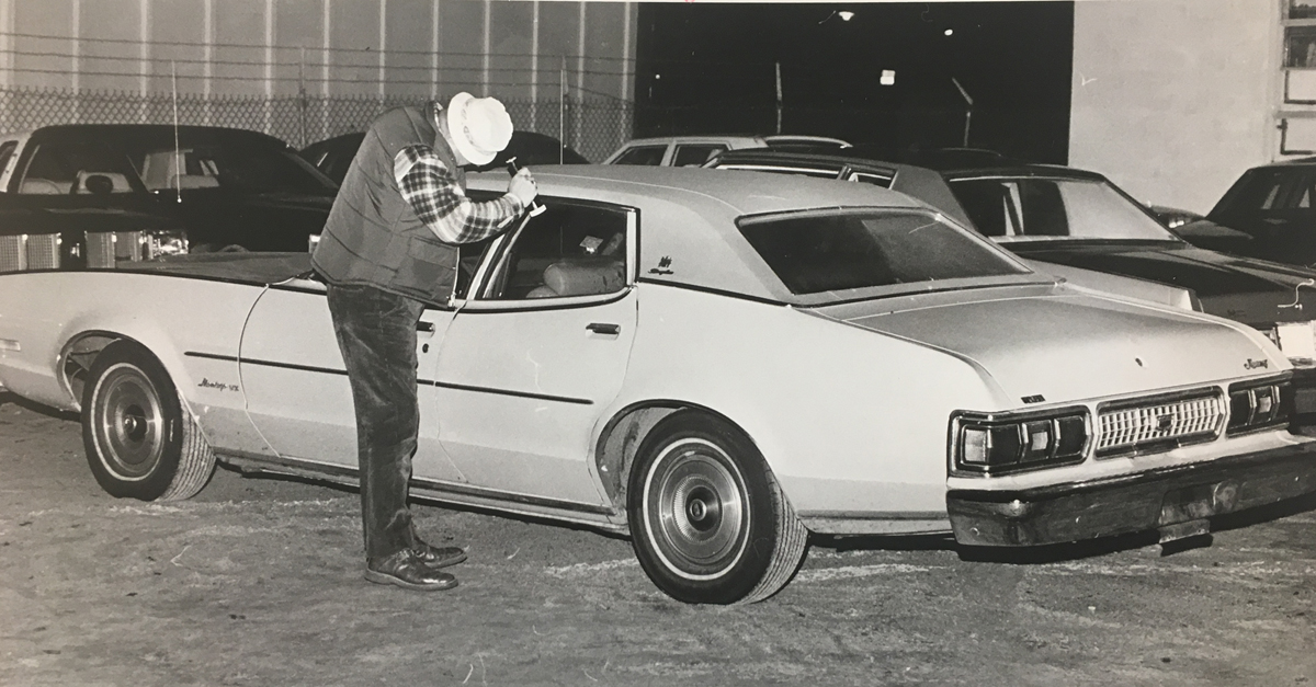 A policeman examines the yellow 1974 Mercury in which George Basmajian's bullet-riddled body was found. Basmajian was sitting in the backseat when he was shot nine times in the torso and face. One detective said the car was steaming up inside when it was discovered.  Courtesy of the Providence Journal/William K. Daby .