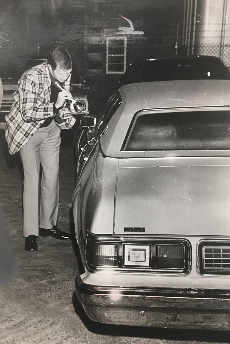 Another policeman shines a flashlight into the Mercury where George Basmajian was murdered.  Courtesy of the Providence Journal/William K. Daby.