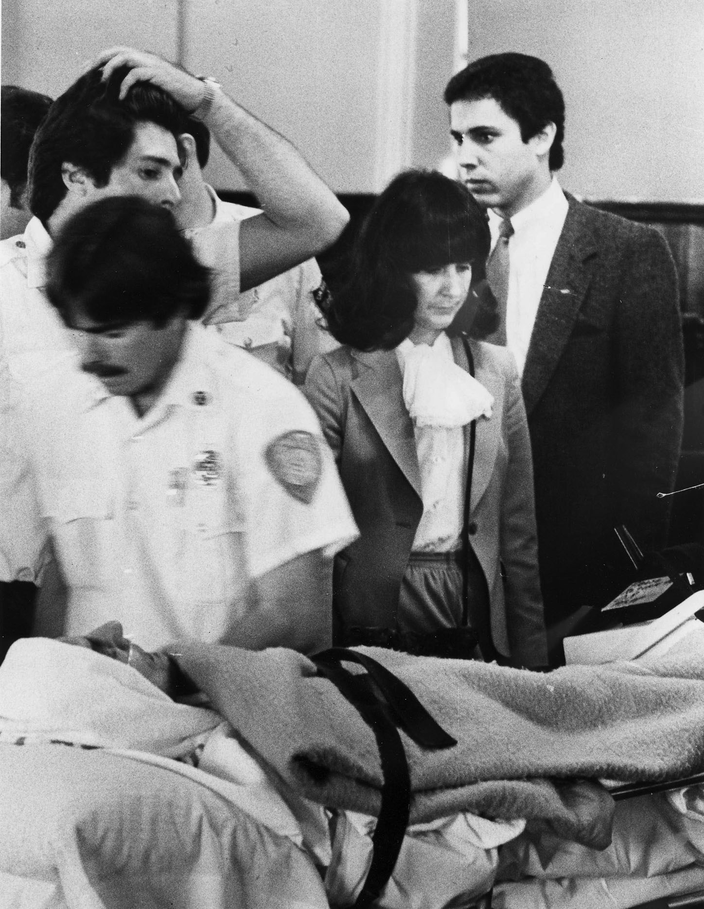 A pale Raymond Patriarca, swathed in sheets and carried on a stretcher, is accompanied by Dr. Barbara Roberts and other medical personnel at his arraignment in March 1981.  Courtesy of The Providence Journal.