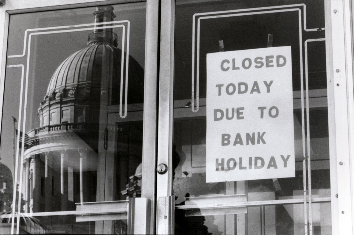 The State House is mirrored in the doorway of the State Employees Credit Union across the street. The credit union was among those that were closed as part of Governor Bruce Sundlun's banking freeze in 1991. Courtesy of The Providence Journal  .