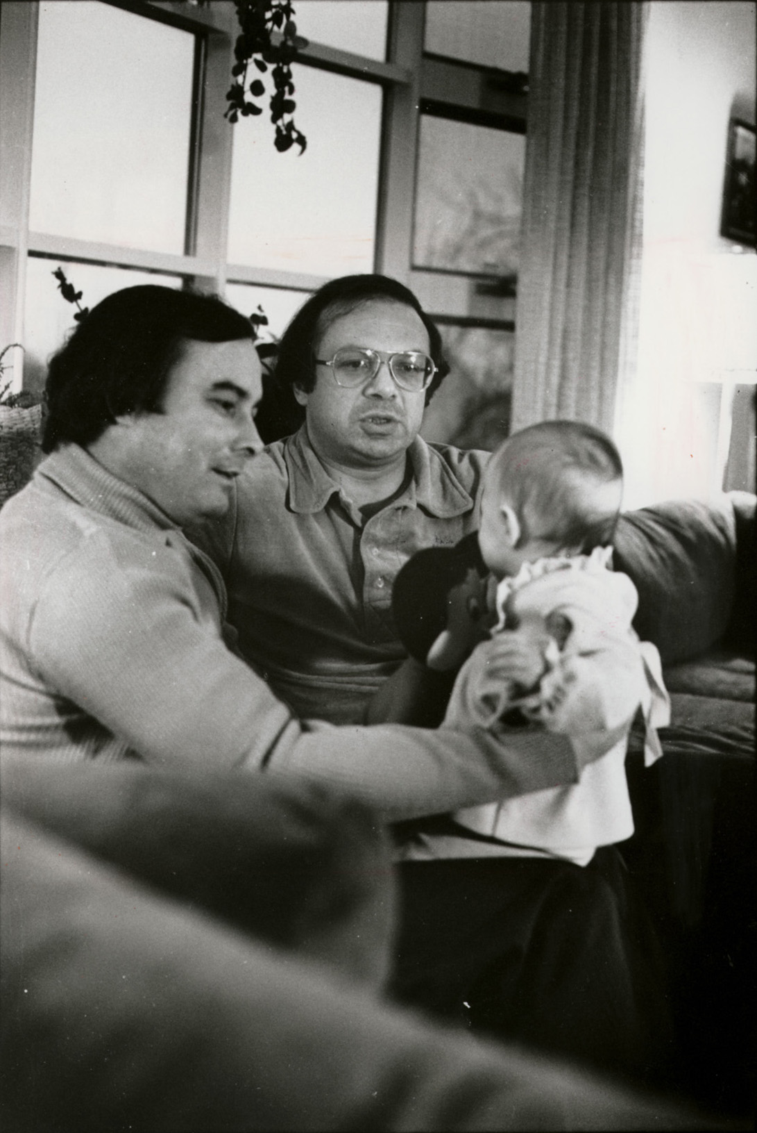 Gerard Ouimette holds his daughter Nicole while lawyer Jack Cicilline, the girl's godfather, looks on. Special to The Providence Journal/Tracy Breton.
