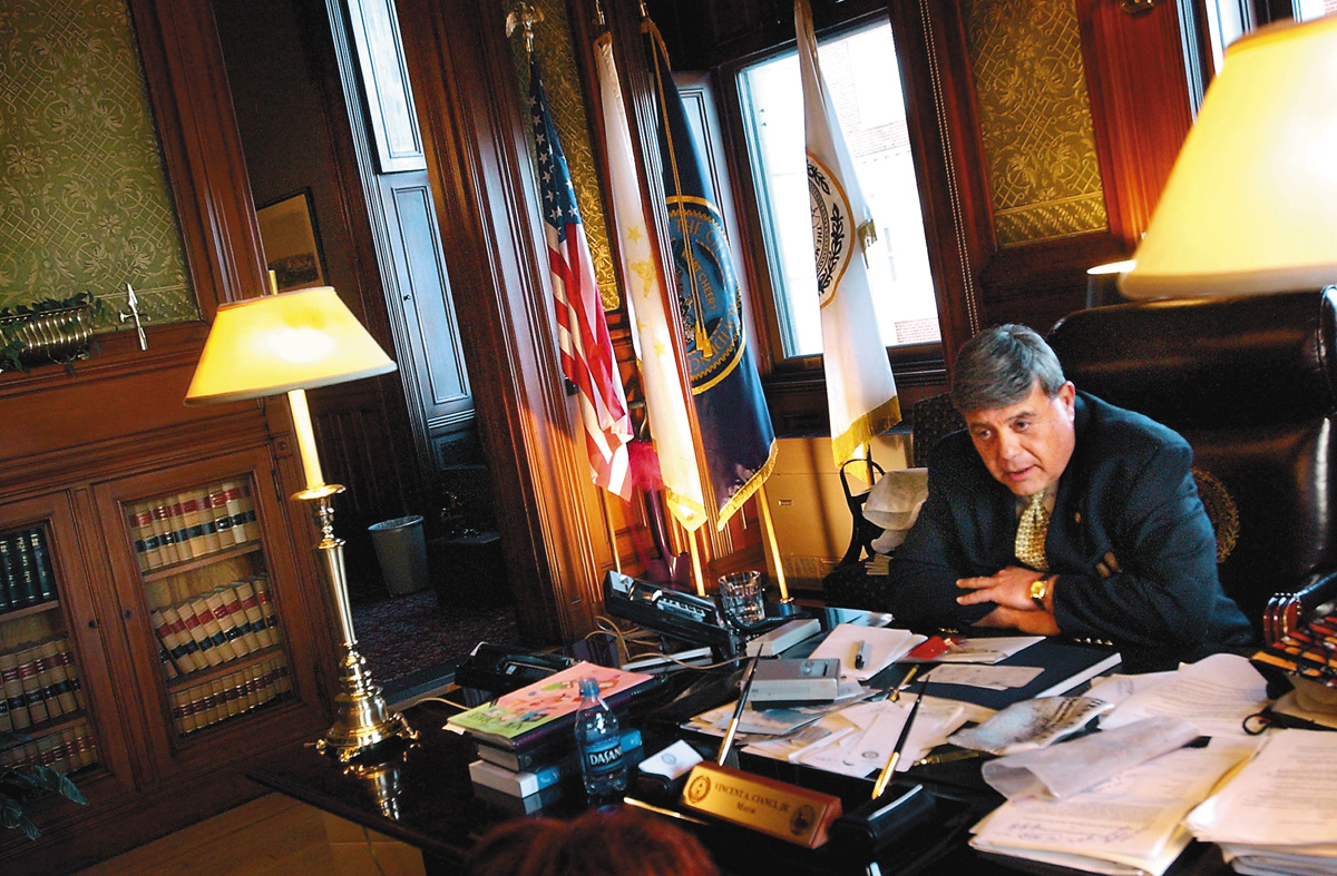 Mayor Buddy Cianci sits at his desk on his last day in office, September 5, 2002. The following day, he was driven to his sentencing in a city-owned Lincoln Town Car. Afterwards, he was driven home in a staffer's beat-up Nissan Maxima.  Courtesy of The Providence Journal/Mary Murphy.