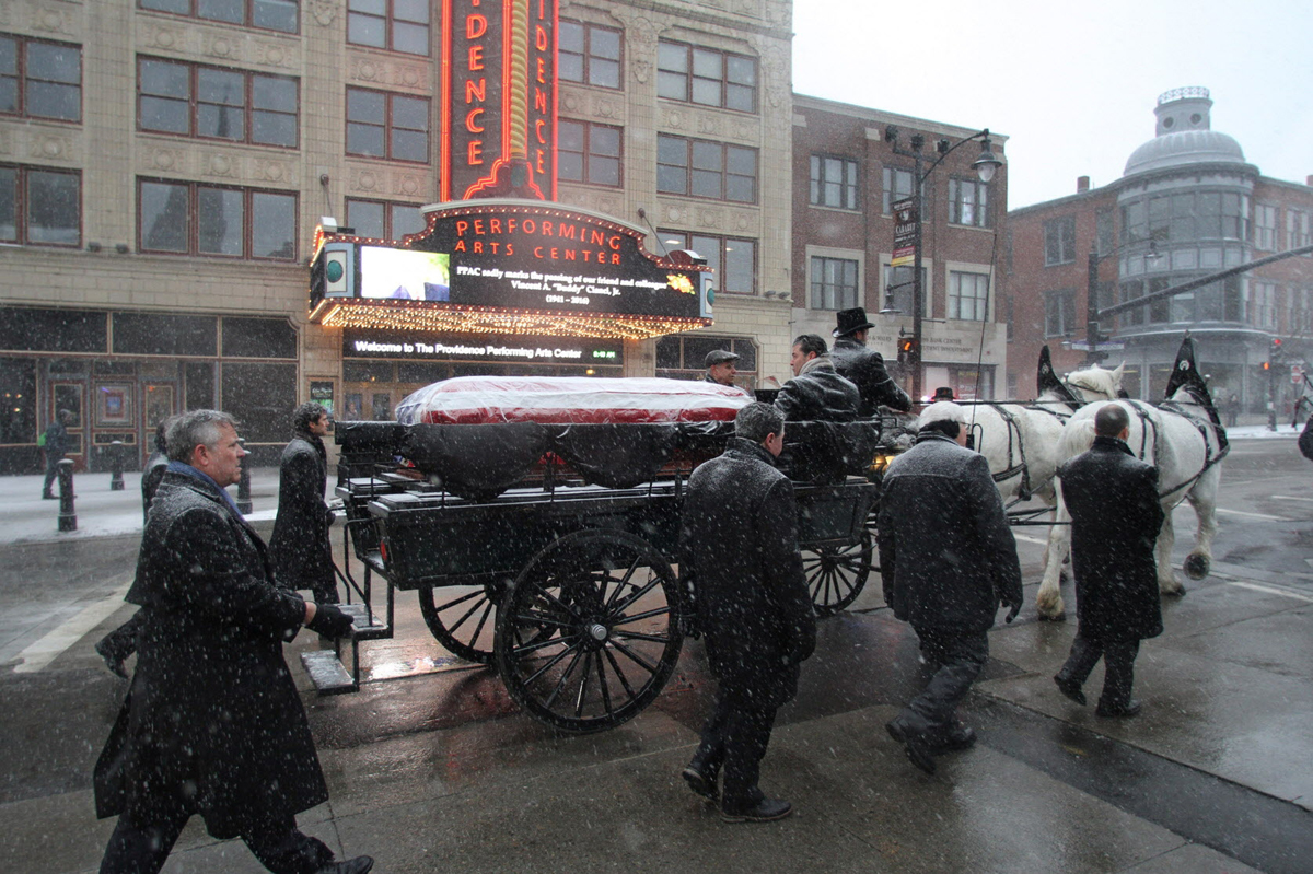 Joseph Paolino, left, and others walk beside the horse-drawn carriage carrying Buddy Cianci's body on the way to the Cathedral of Saints Peter and Paul.  Courtesy of The Providence Journal/Steve Szydlowski.