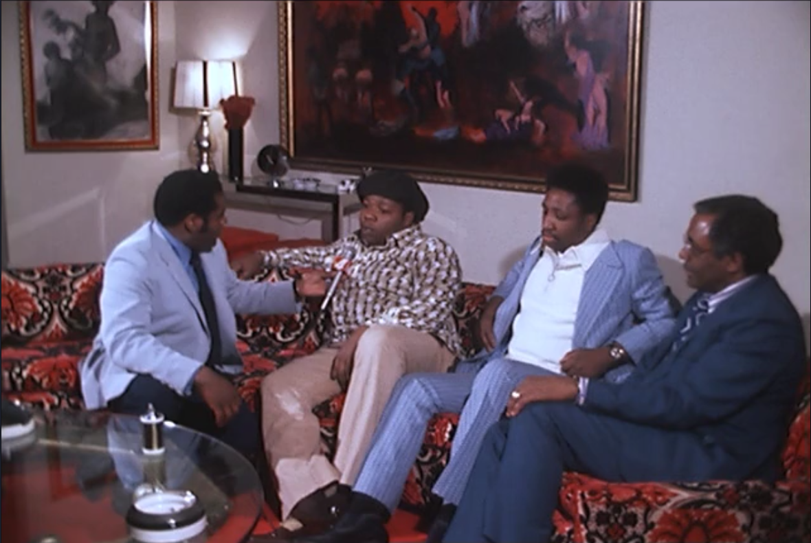 When the federal indictment came down, news reporters took an interest in Eddie Jackson Sr. and Courtney Brown Sr. In this photo, Eddie and Courtney are talking with reporter Bob Bennett (left), accompanied by their lawyer (right). This interview was conducted in Eddie Jackson's living room, which featured a custom painting of black people slaughtering white people.  Courtesy of the Walter P. Reuther Library at Wayne State University.