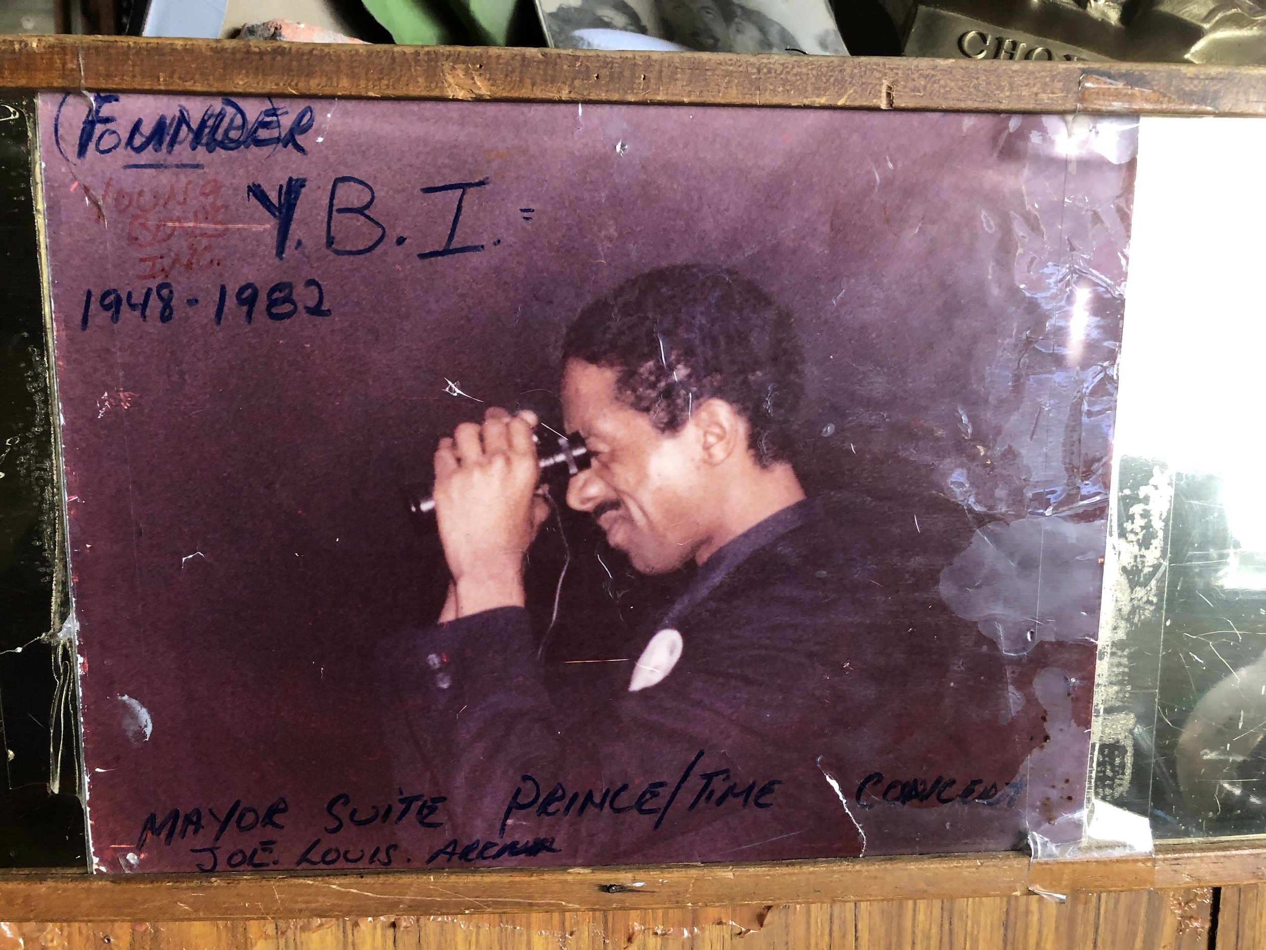 """As a drug supplier to Young Boys Incorporated, Benji Mongo could afford to live lavishly. In this photo, which hangs in Cafe D'Mongo's, Benji is observing a Prince concert from the Mayoral Suite of the Joe Louis Arena.   But when his youngest brother, Skip, started hanging out with Dwayne """"Wonderful Wayne"""" Davis of YBI, Benji made it clear that he did not want Skip in the drug world.  Photo by Drew Nelles."""