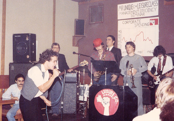 George Mugianis, left, often went to Leisure Class shows to see his brother Dimitri, second from left. Here, the band performs at Bunches in East Lansing, Michigan in 1982. The band was known for theatrical and confrontational live shows, which garnered them some local renown, though Dimitri says his drug use impeded their success.  Courtesy of Dimitri Mugianis.