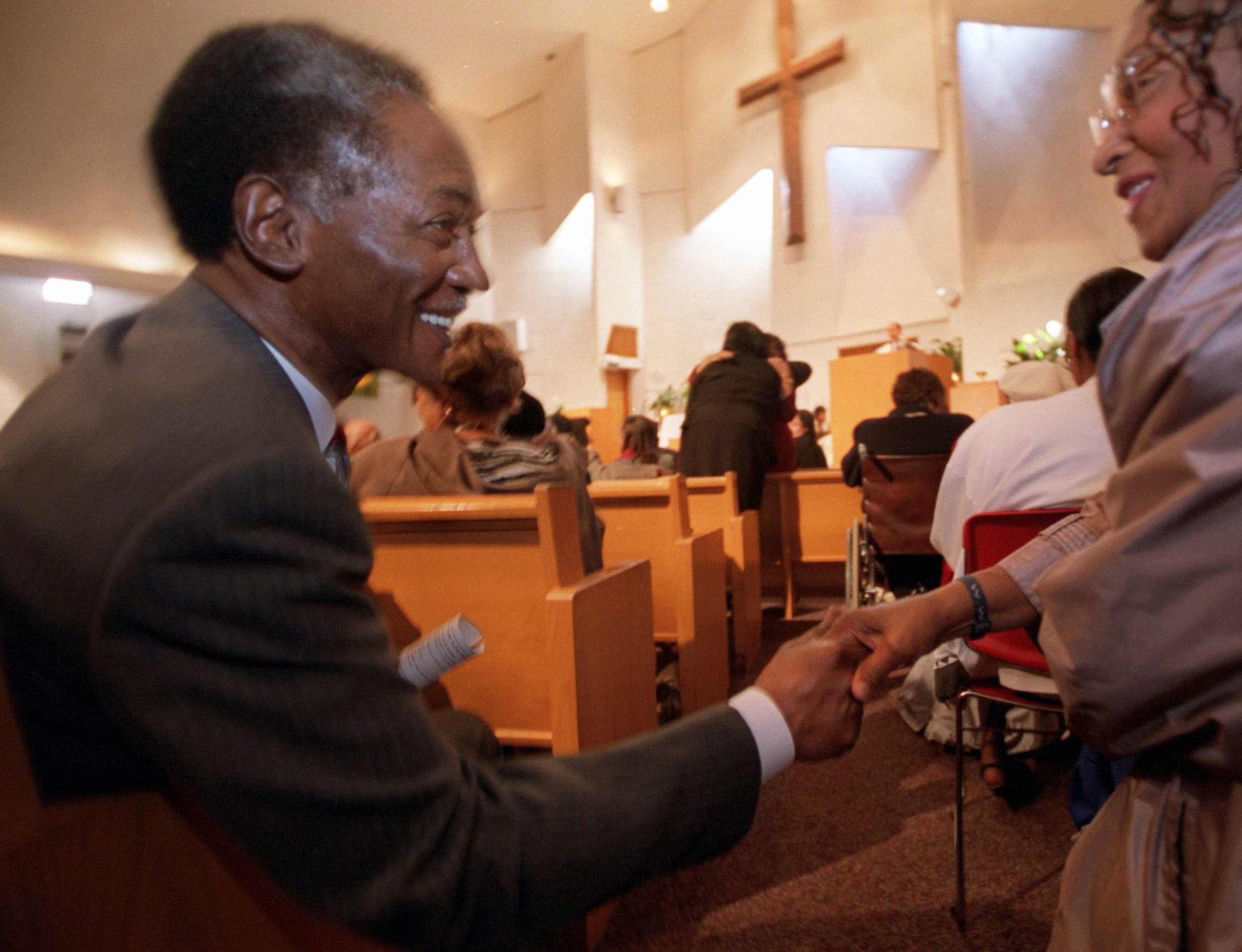 Gil Hill shakes hands with a congregation member at Plymouth Congregational Church in Detroit on Sunday, November 4, 2001 two days before the general election.  Courtesy of the Detroit Free Press.