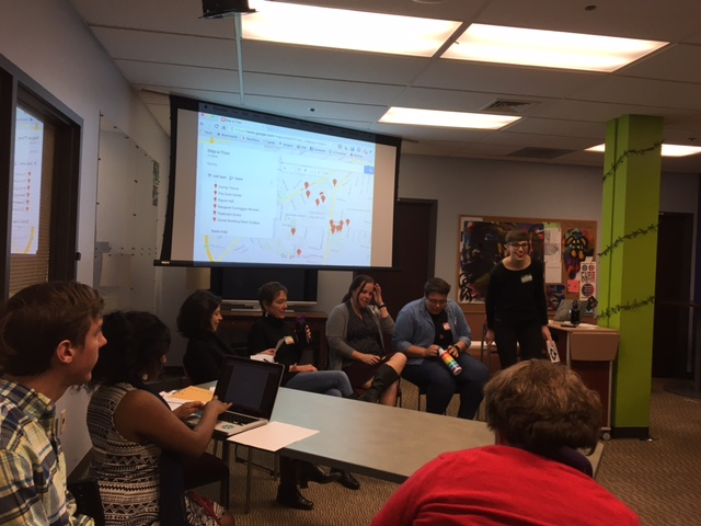 [Image description: a panel of educators sits in front of a projector screen, which shows a map with red dots. They address an audience of students who take notes in the foreground]