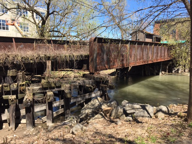 [Image description: A rusted steel bridge held up by wooden supports goes over a stretch of creek with muddy water. Trees in the background are just beginning to bloom and the sky is clear blue. A few buildings are visible in the distance.]