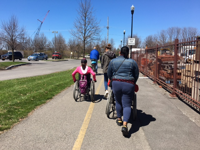 """[Image description: Participants in the workshop (including two walkers, two wheelchair users, and a cyclist, move along a stretch of paved road in front of a rusted metal fence. On the left is a strip of grass and a parking lot. A construction crane and a line of bare trees are in the distance. A sign on a street light says """"watch for vehicles.""""]"""