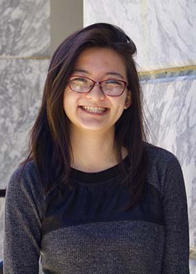 [Image description: a lightly tan person with medium-length dark brown hair parted to the right looks straight at the camera. She is smiling with teeth and wears a pair of red glasses. Her photo crops below the elbow and she is wearing a grey, long-sleeved shirt with a block of black near the top. The background is white marble.]