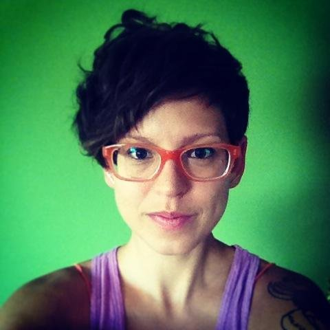 [Image description: a light-skinned person with short dark hair and red glasses looks at the camera, wearing a pink tank top. The background is bright green]