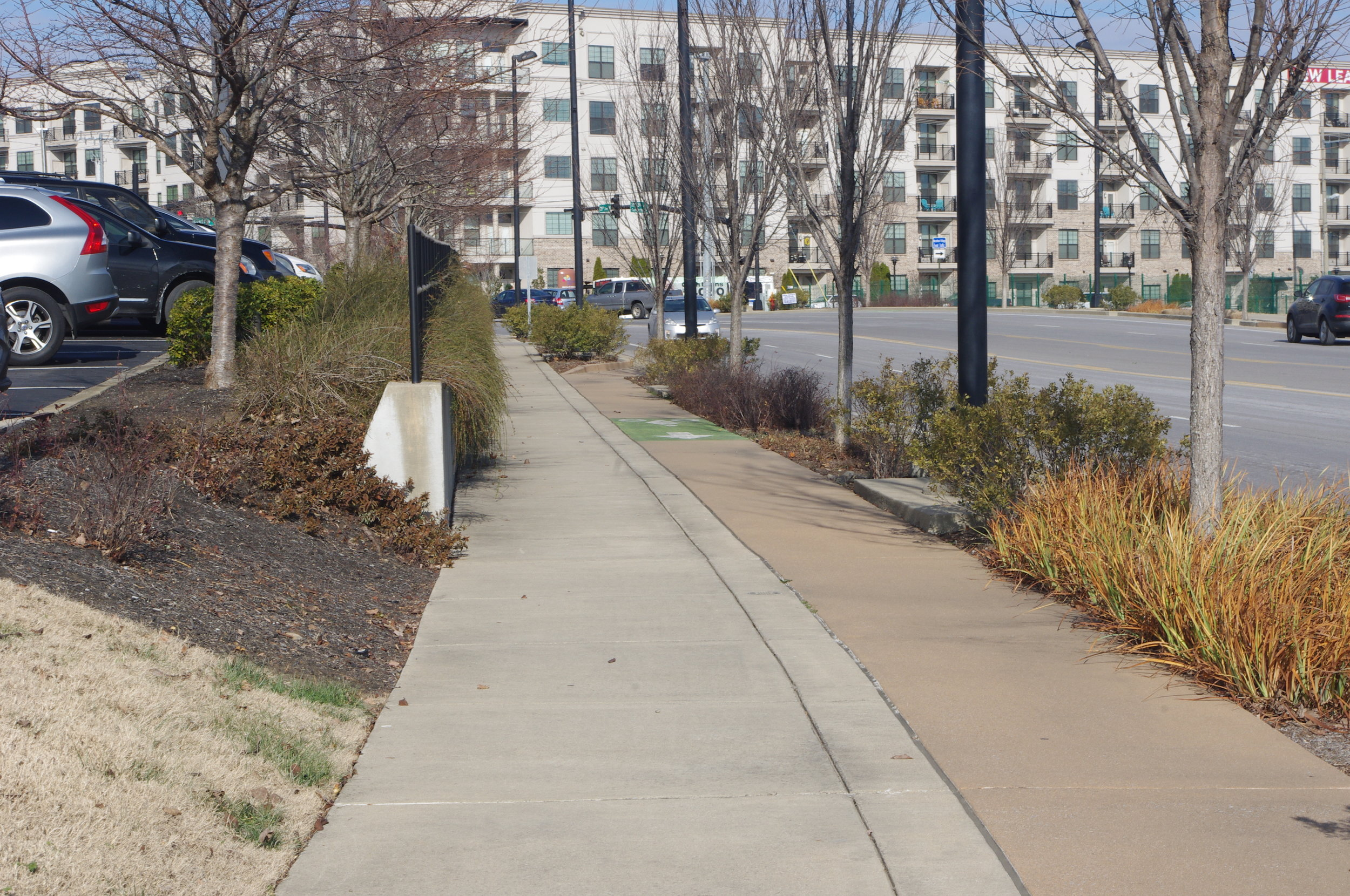 "Image description: a ""complete street"" with paved sidewalks, bicycle lanes, and streets for car traffic, with trees forming a barrier between the bicycle lane and the street. In the background, an apartment building."
