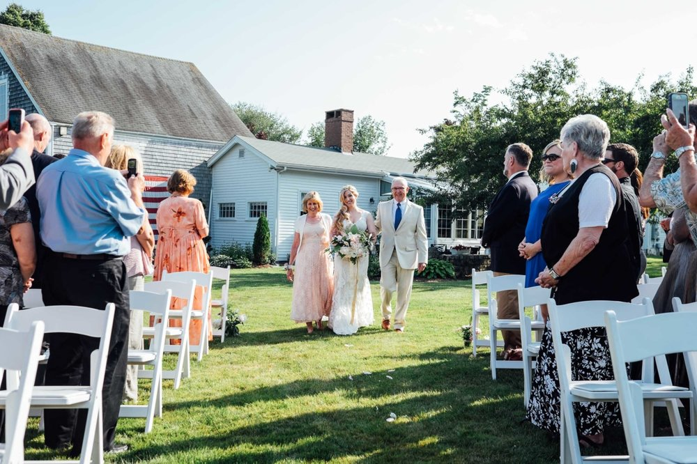 bride walks down natural outdoor aisle