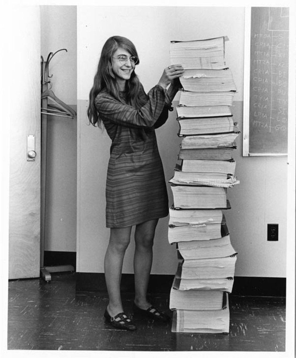 Famed computer scientist Margaret Hamilton standing next to the space mission code she led the development of.